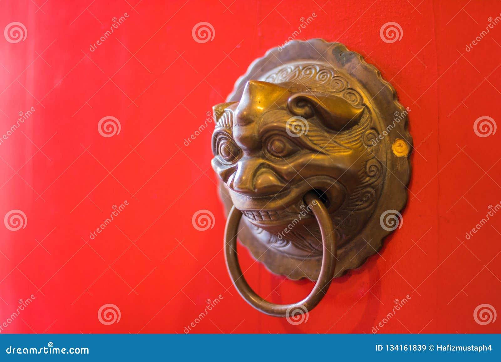Mässingsdörrknackare på den röda dörren av templet