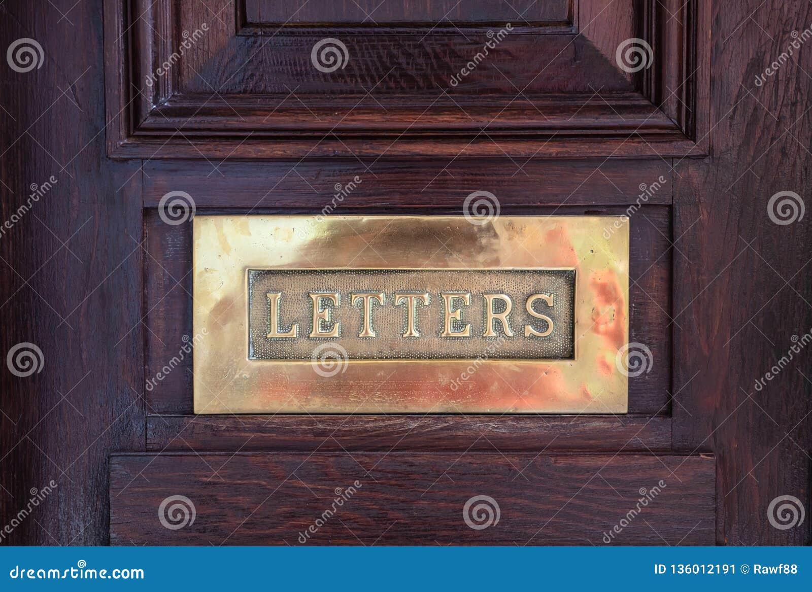 Mässingspostbrevlåda på en träytterdörr, textbokstäver