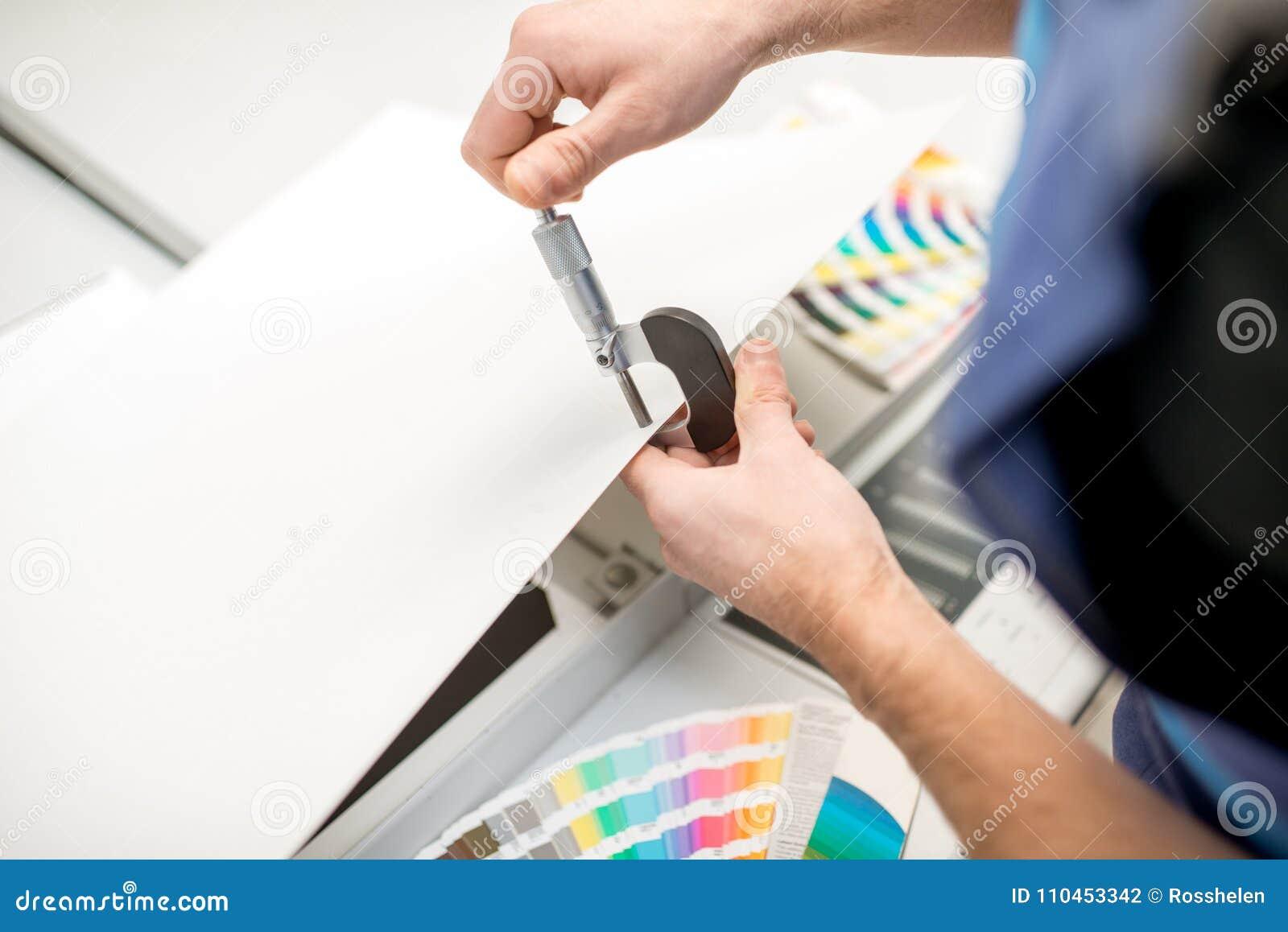 Mäta tjocklek av det pappers- arket med mikrometer