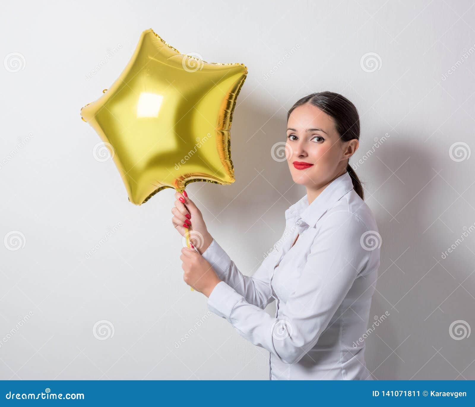 Młoda ładna kobieta trzyma gwiazdę kształtował balon Wakacyjny pojęcie