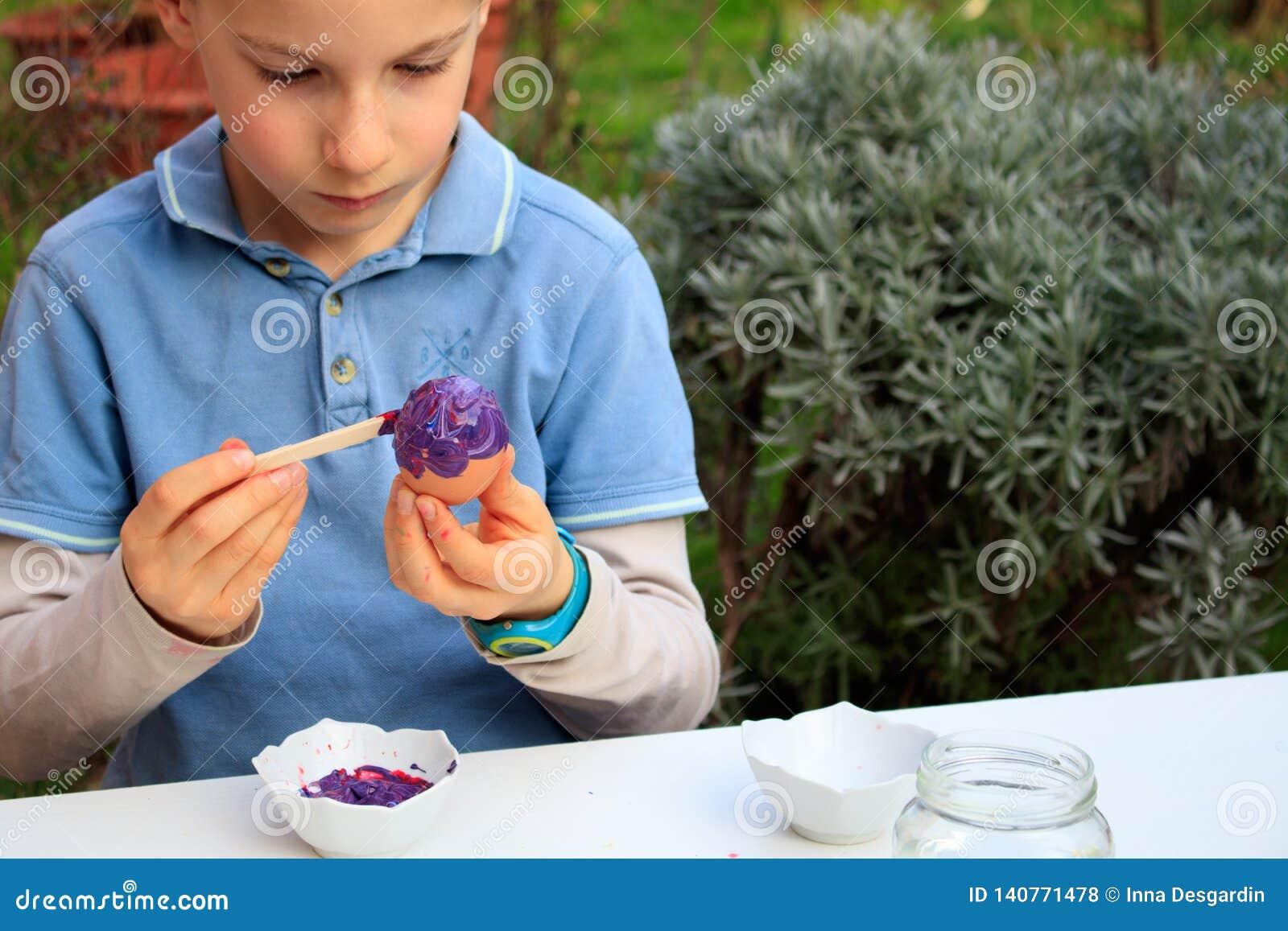 Młoda chłopiec maluje Wielkanocnych jajka plenerowych w Francja Wielkanocnych dzieci kreatywnie aktywność