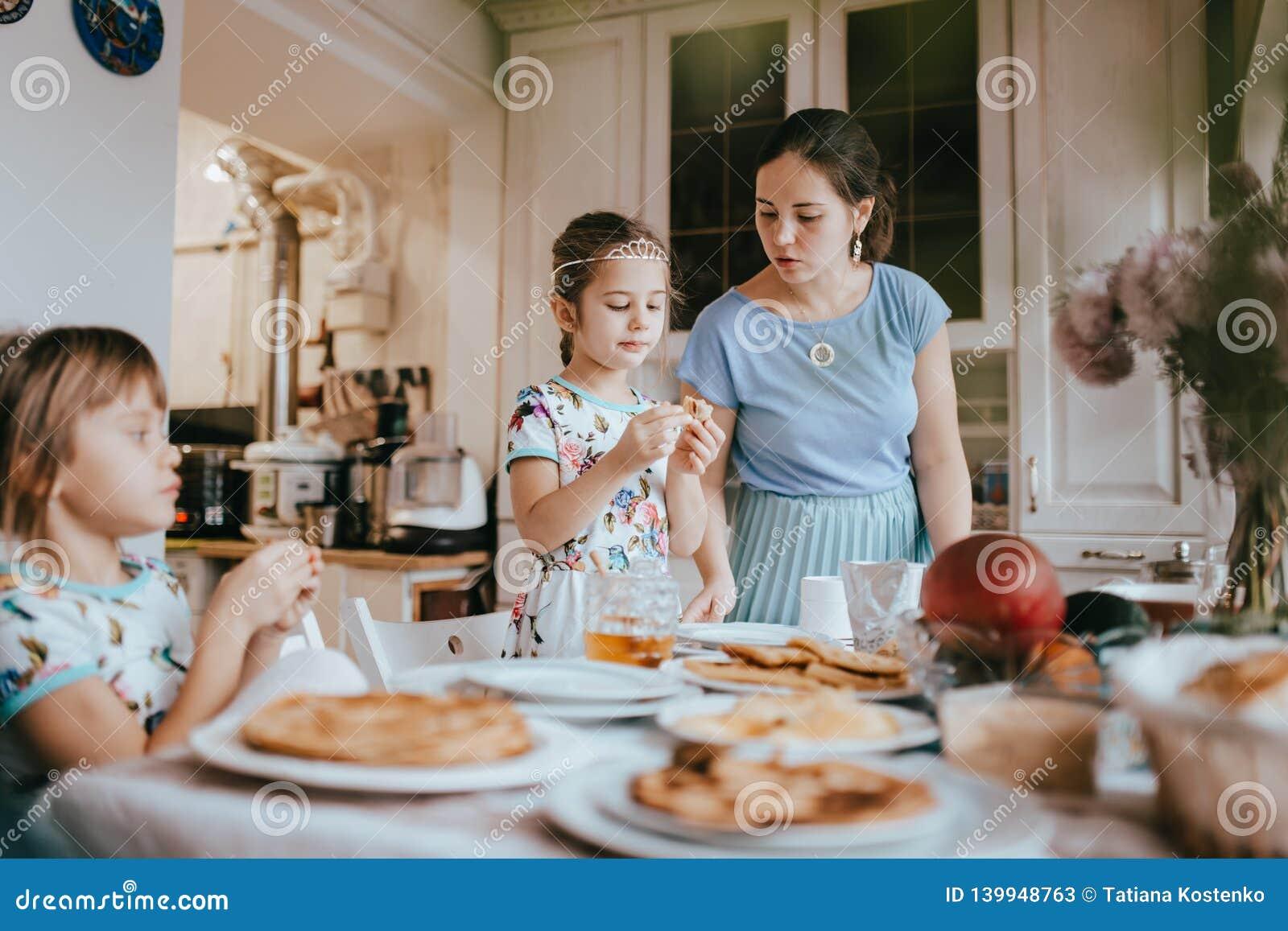Młoda czułości matka i jej dwa małej córki je bliny z miodem przy śniadaniem w wygodnej kuchni