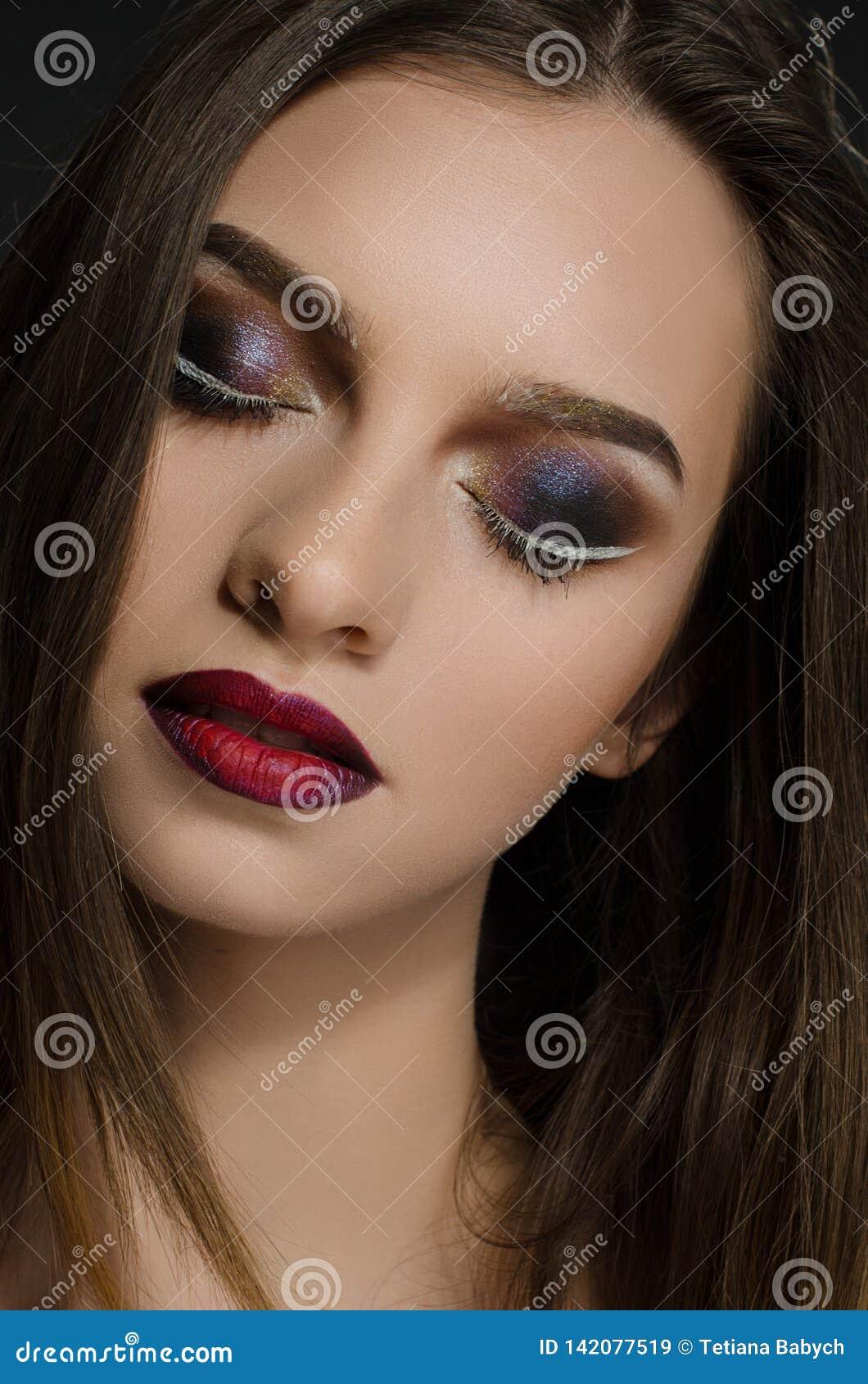 Młoda dorosła dziewczyna z pięknym wieczór makeup na czarnym tle