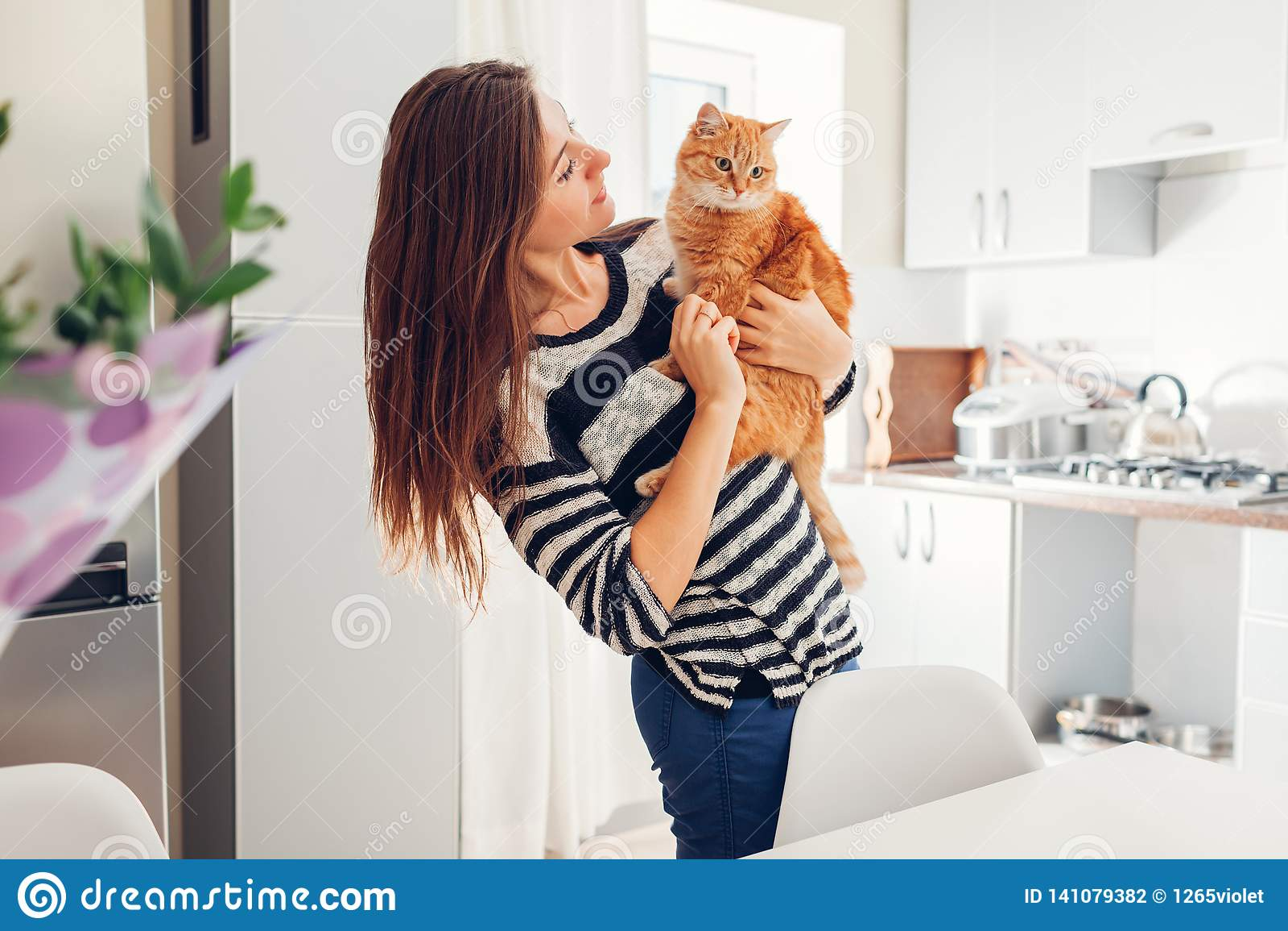 Młoda kobieta bawić się z kotem w kuchni w domu Dziewczyny mienia i przytulenie imbiru kot