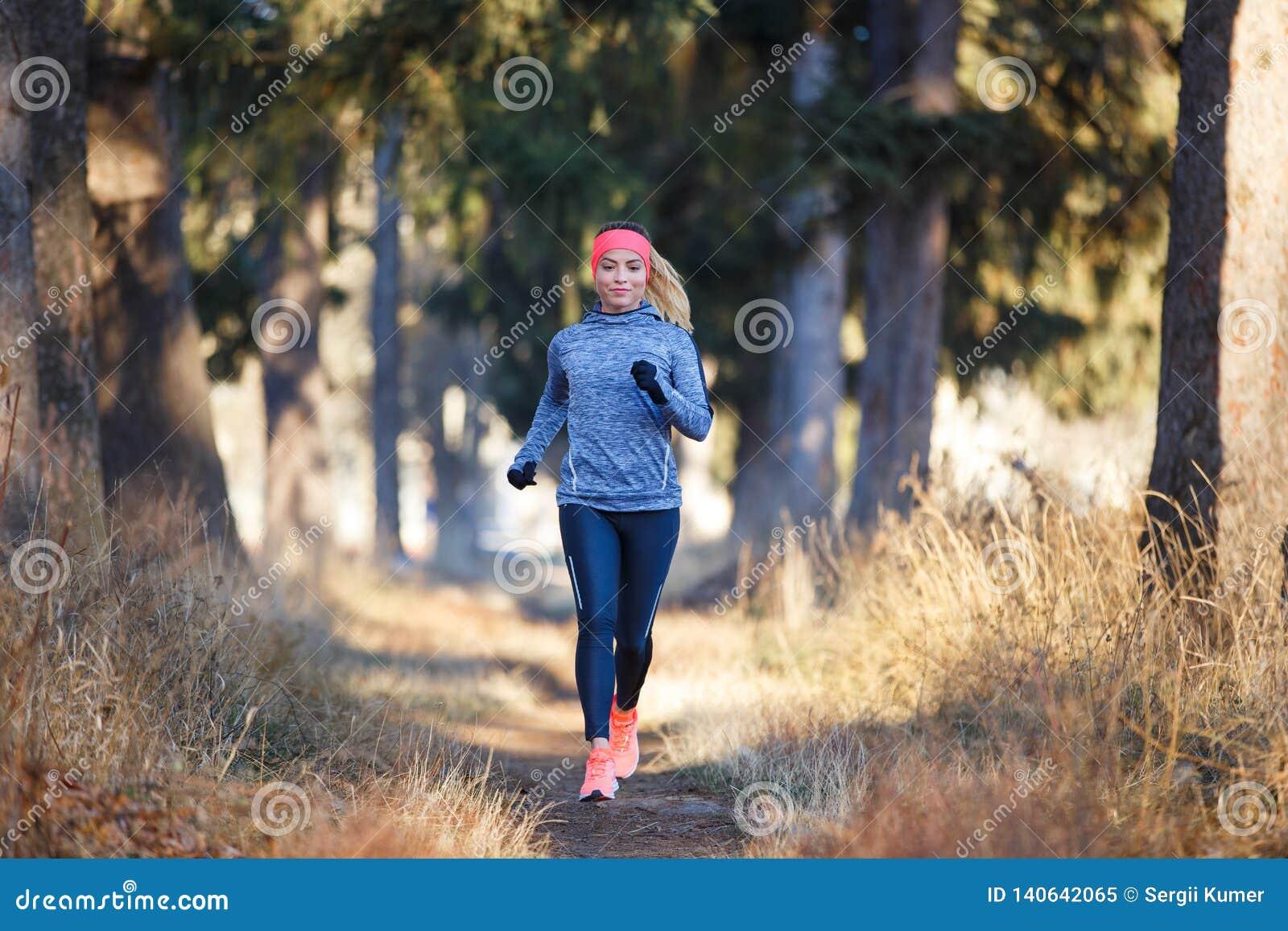 Młoda kobieta jogging na śladzie w jesień parku