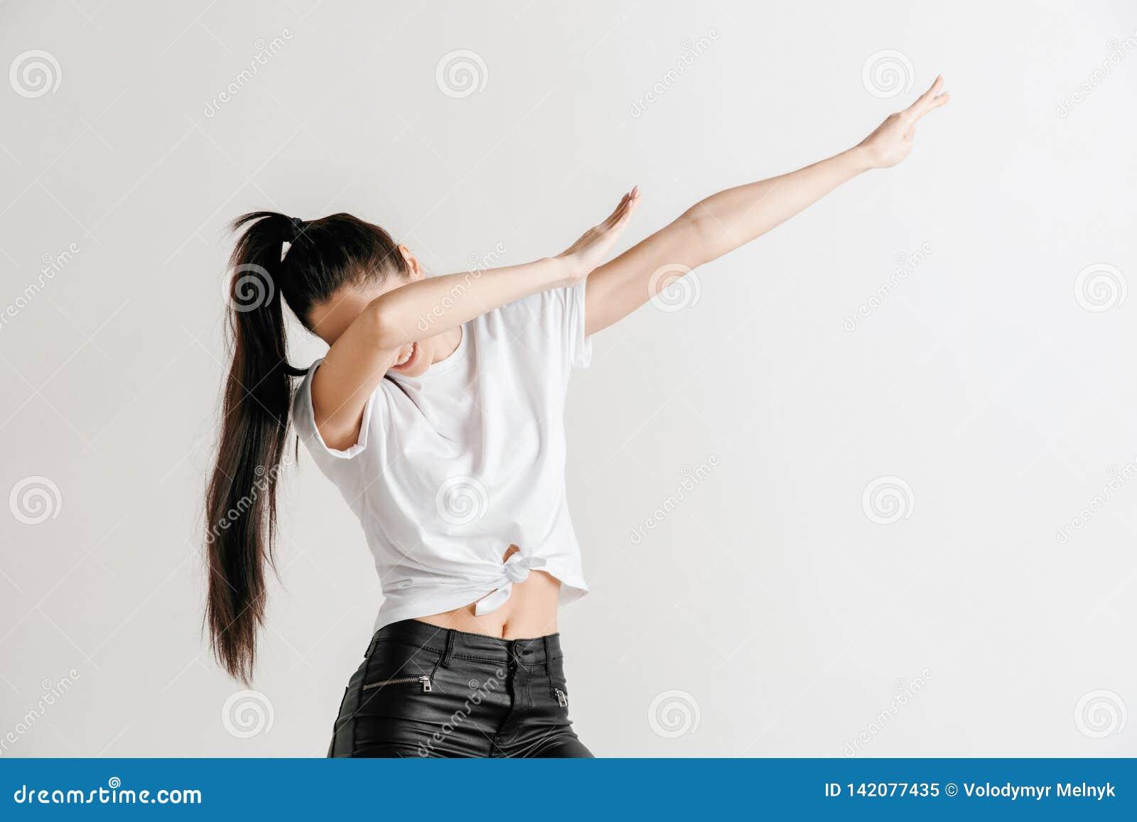 Młoda kobieta robi odrobina ruchu z jego rękami na szarym tle