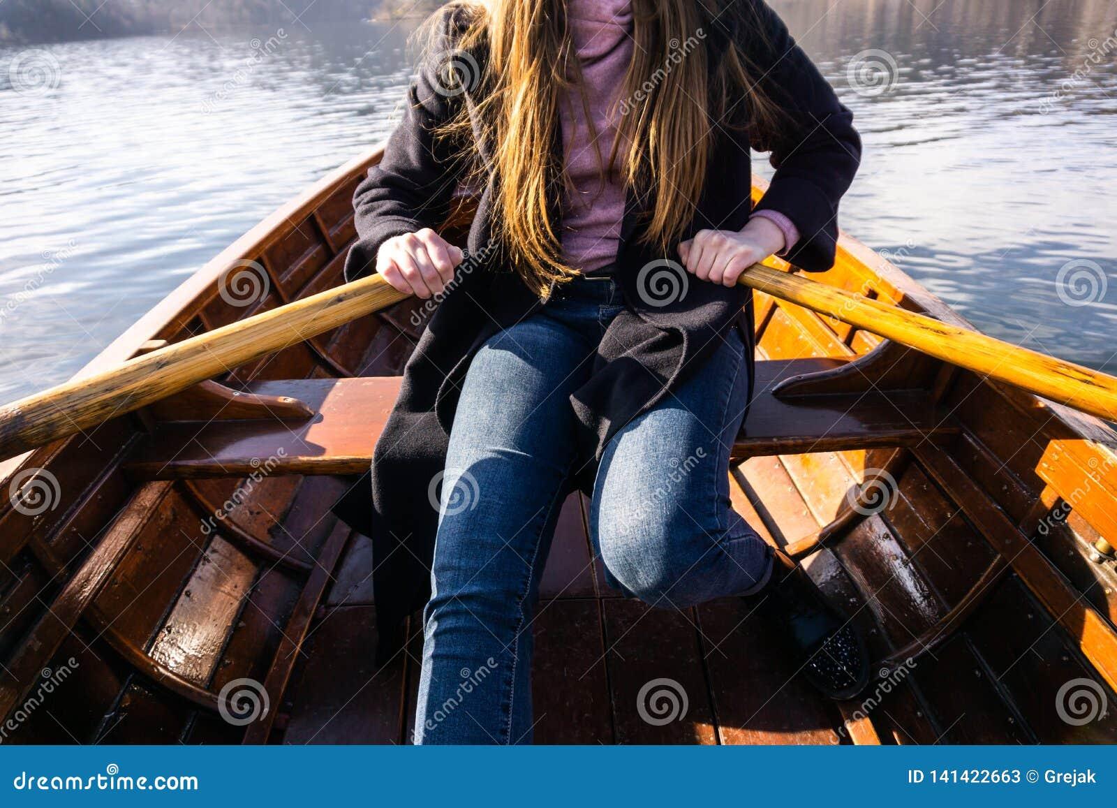 Młoda kobieta używa paddle na drewnianej łodzi - jezioro Krwawił Slovenia wioślarstwo na drewnianych łodziach