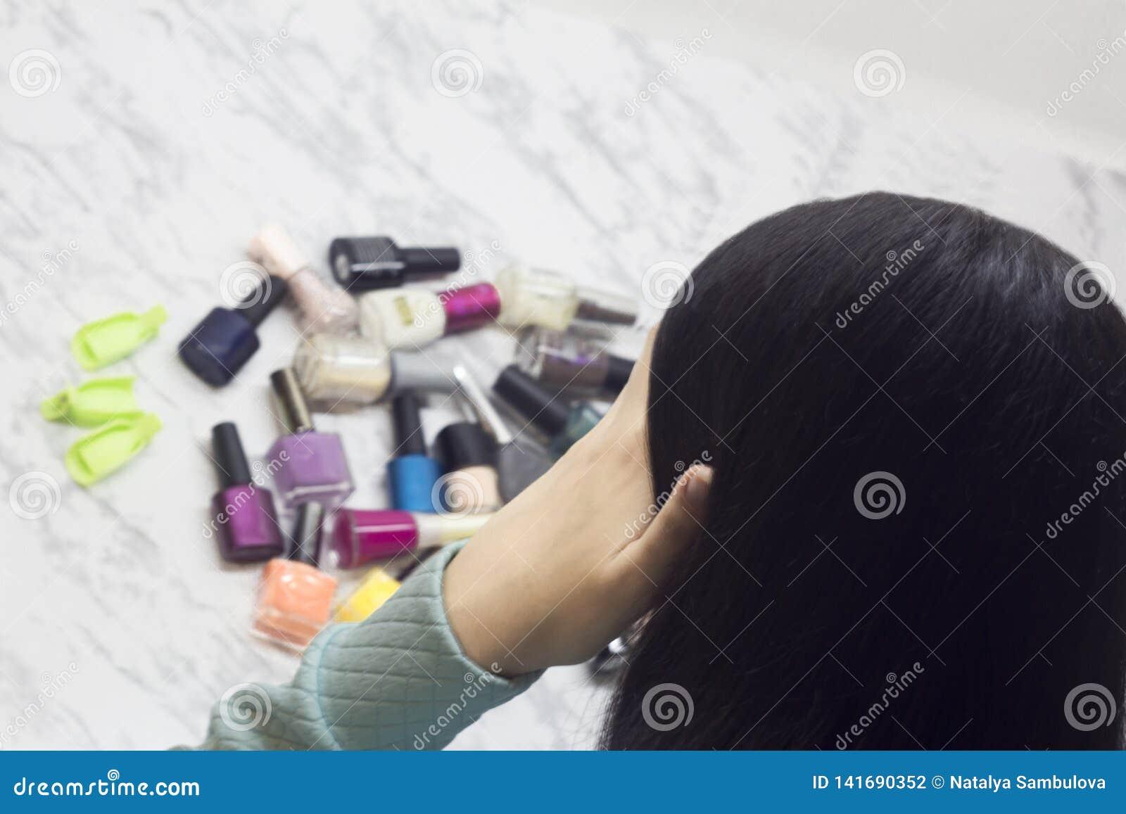 Młoda kobieta wybiera gwoździ połysk, piękno i modę, trudność wybór, dylemat, zdroju salon w domu