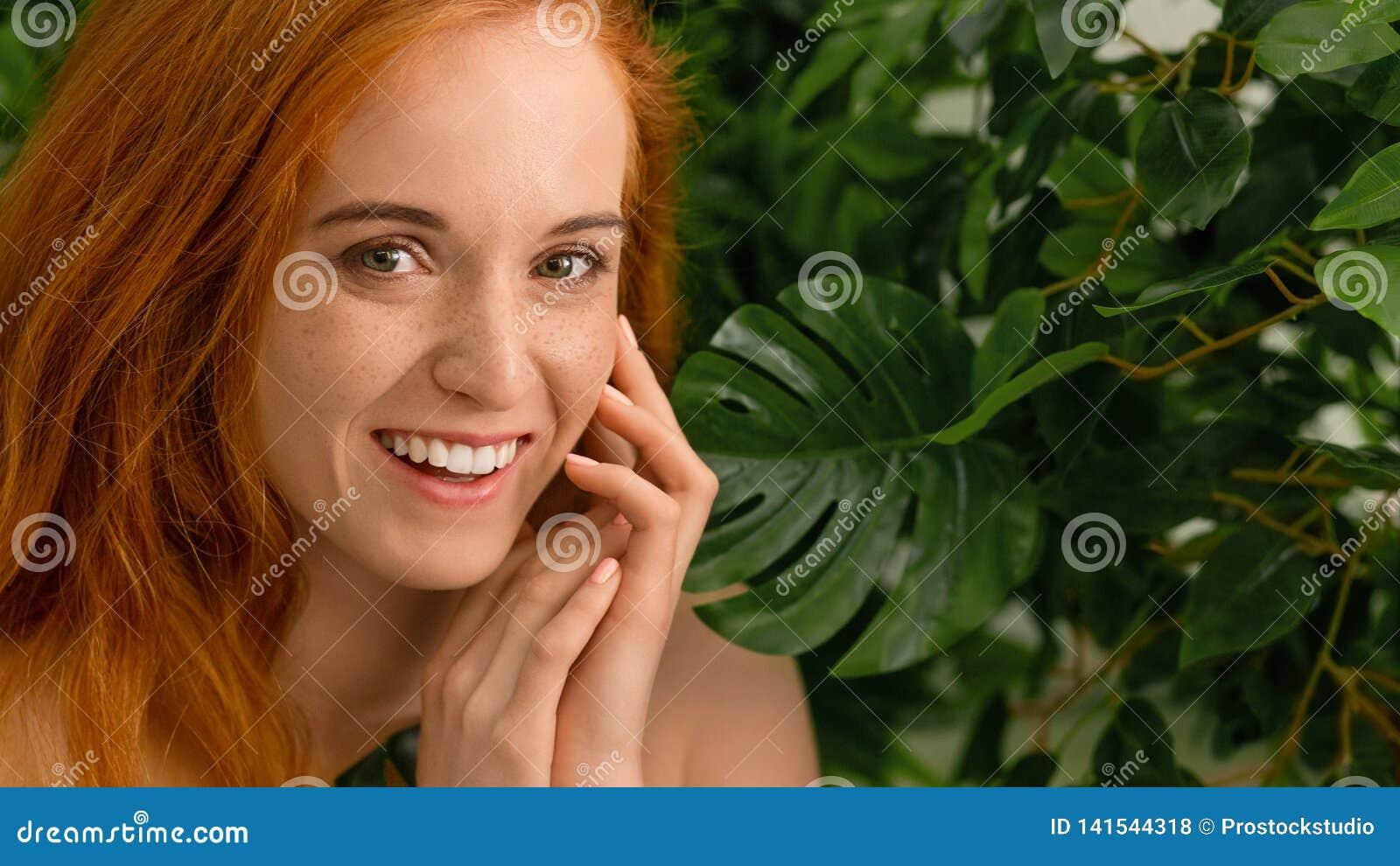 Młoda kobieta z doskonalić uśmiechem na z zielonym natury tłem