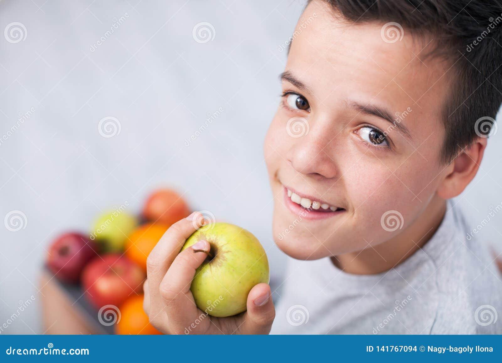 Młoda nastolatek chłopiec trzyma jabłka - przyglądający w górę