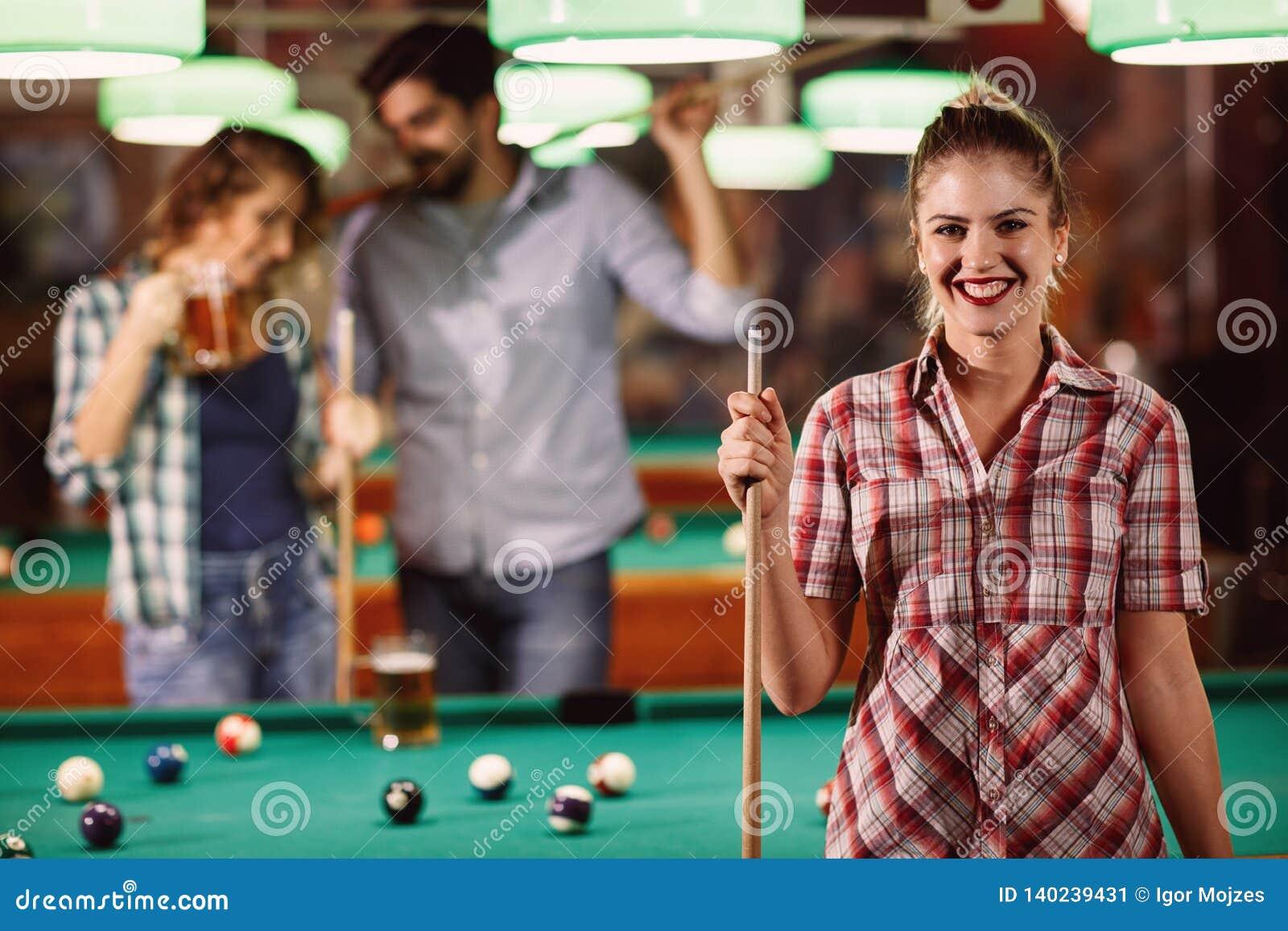 Młoda piękna dziewczyna w bilardowym klubie z wskazówka kijem