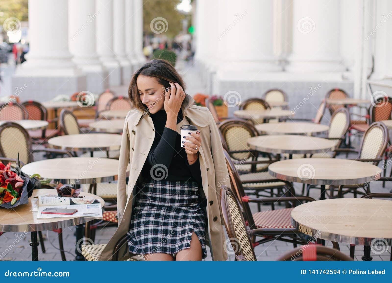 Młoda piękna kobieta pije kawę w ulicznej kawiarni