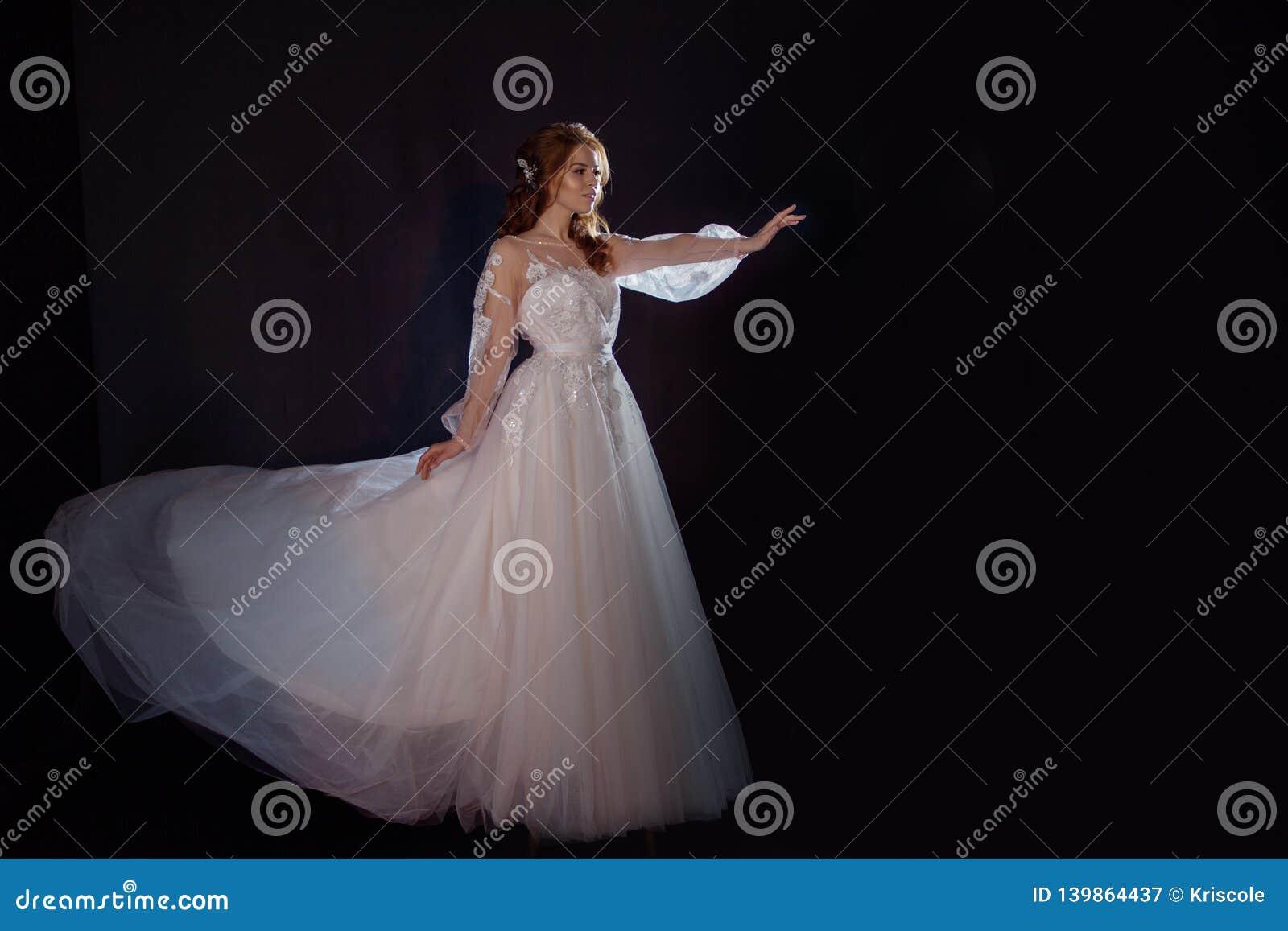Młoda piękna kobieta w ślubnej sukni z szeroką światło spódnicą Ciemny tło, fantazja styl
