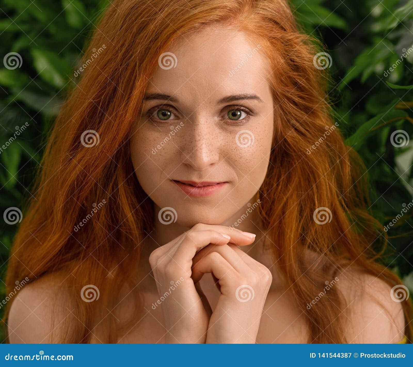 Młoda rudzielec dziewczyna patrzeje kamerę, zieleń opuszcza tło