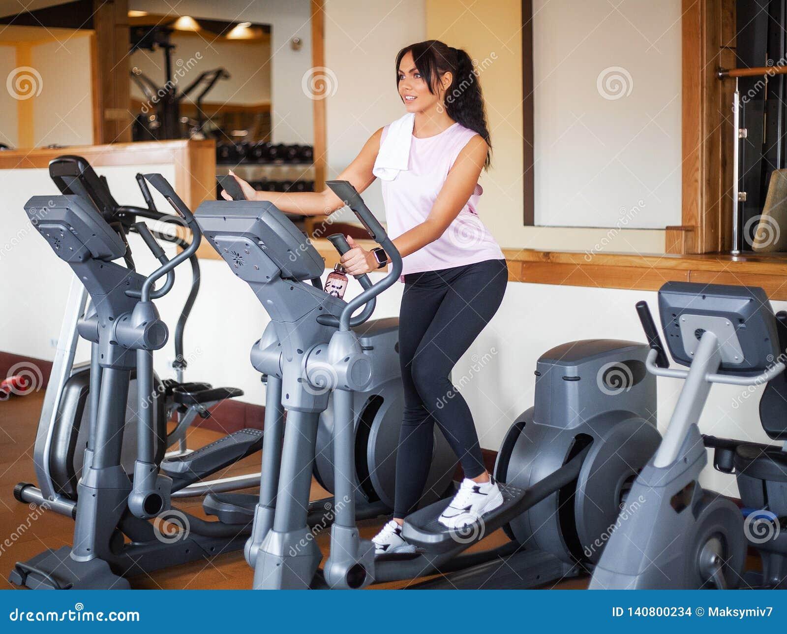 Młoda sprawności fizycznej kobieta opracowywa w gym Kobieta pracująca na ćwiczenie rowerze out
