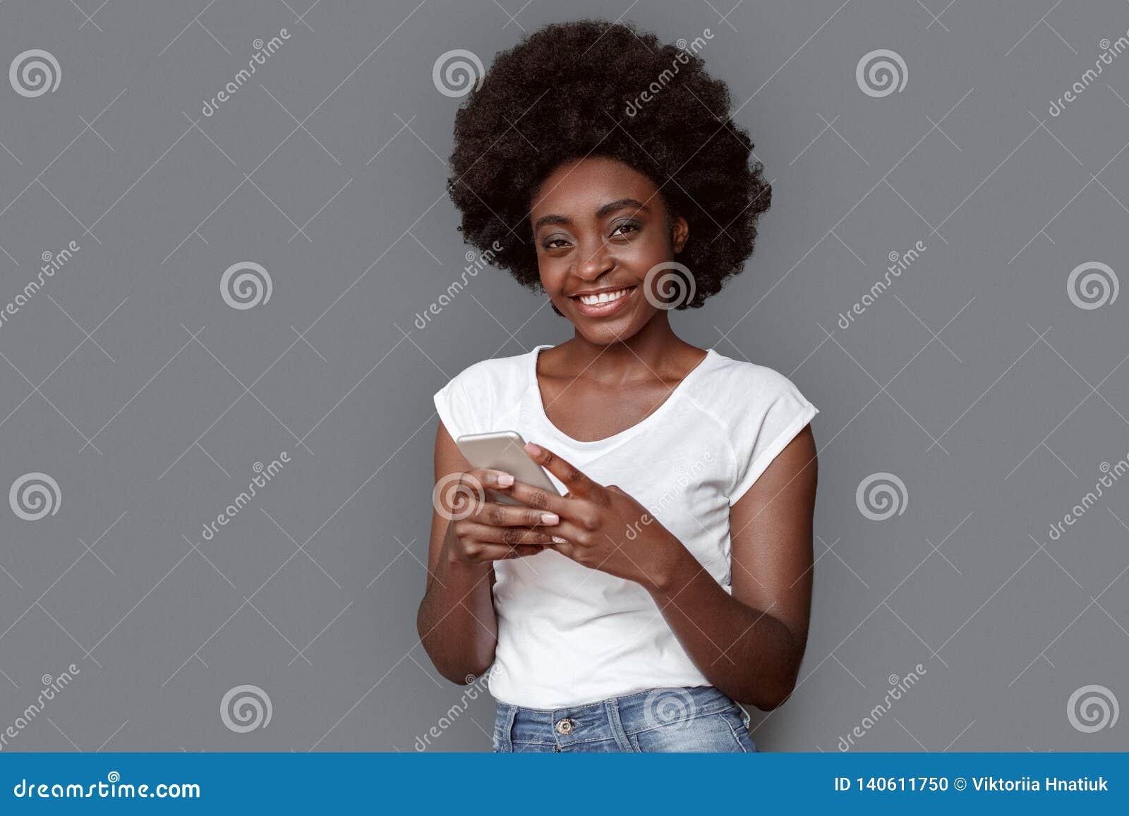 Młodej kobiety pozycja odizolowywająca na szarej używa smartphone przyglądającej kamerze rozochoconej