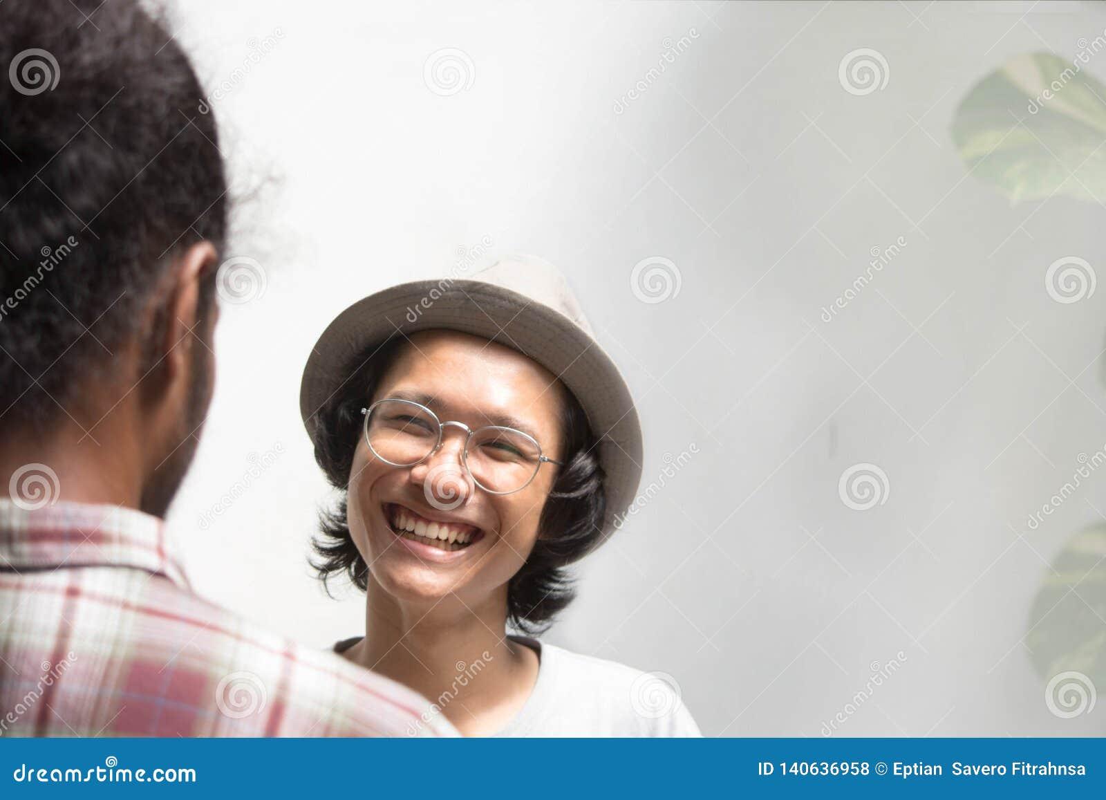 Młody azjatykci męski ręki potrząśnięcie z przyjacielem jako przedpole, młody azjatykci mężczyzna z szkło uściskiem dłoni z murzy