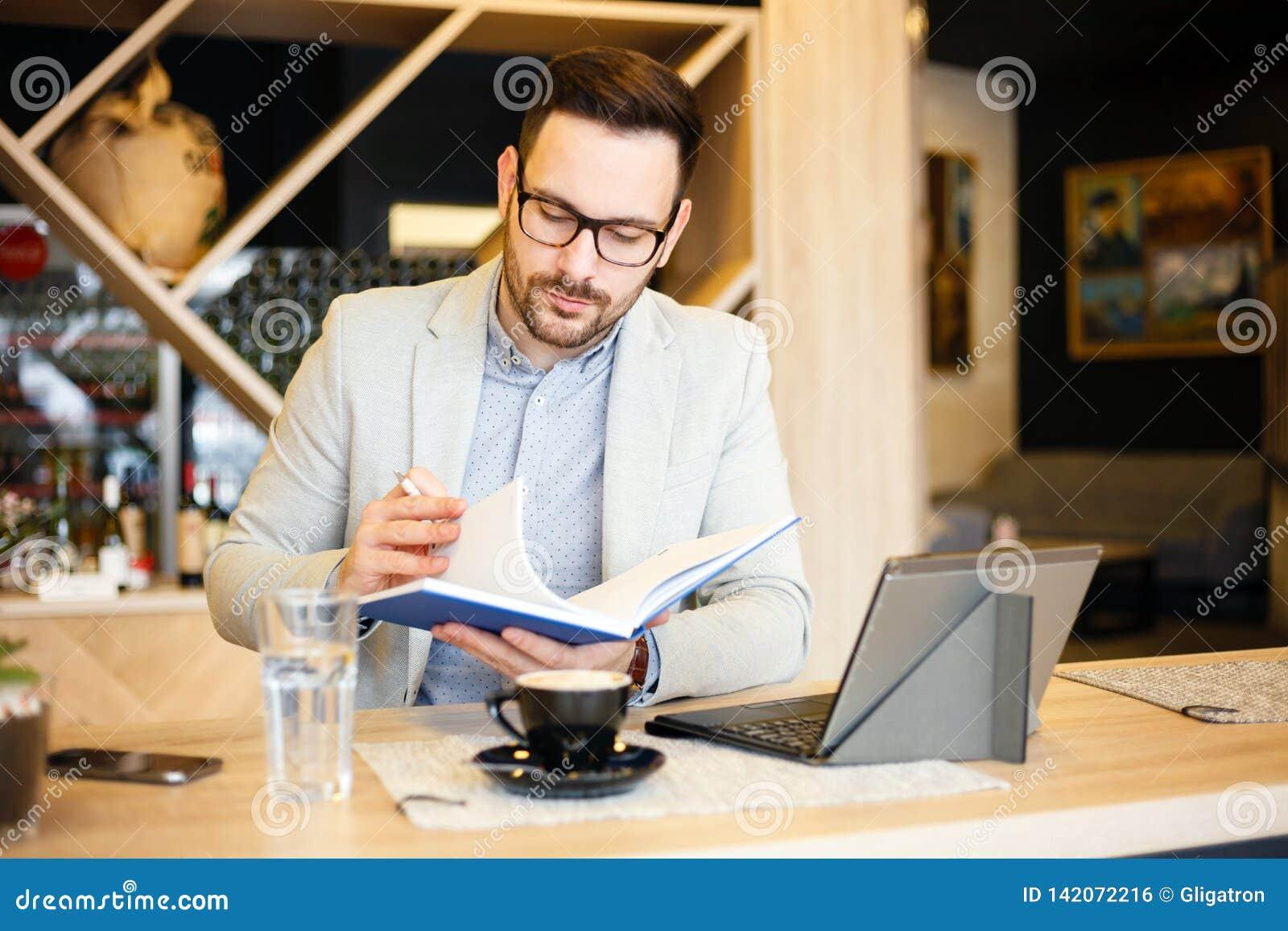 Młody biznesmen sprawdza dzienną agendę w notepad podczas gdy siedzący w nowożytnym sklepie z kawą