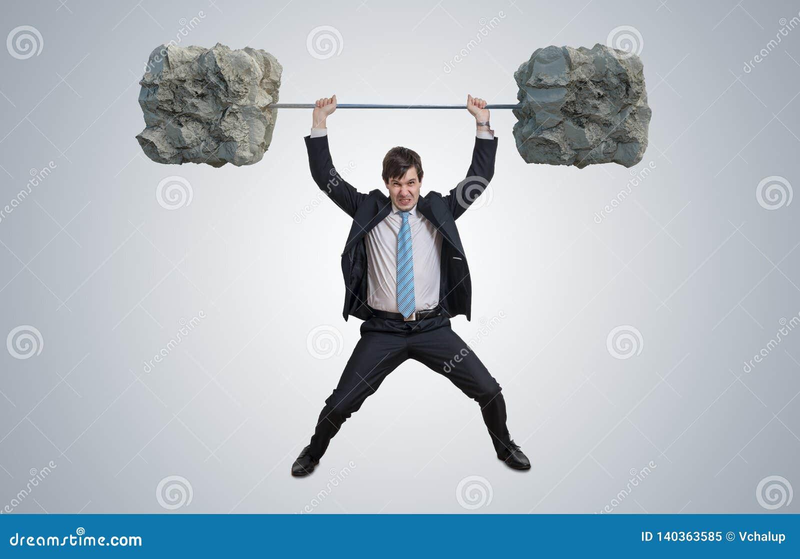 Młody biznesmen w kostiumu jest podnośnymi ciężkimi ciężarami