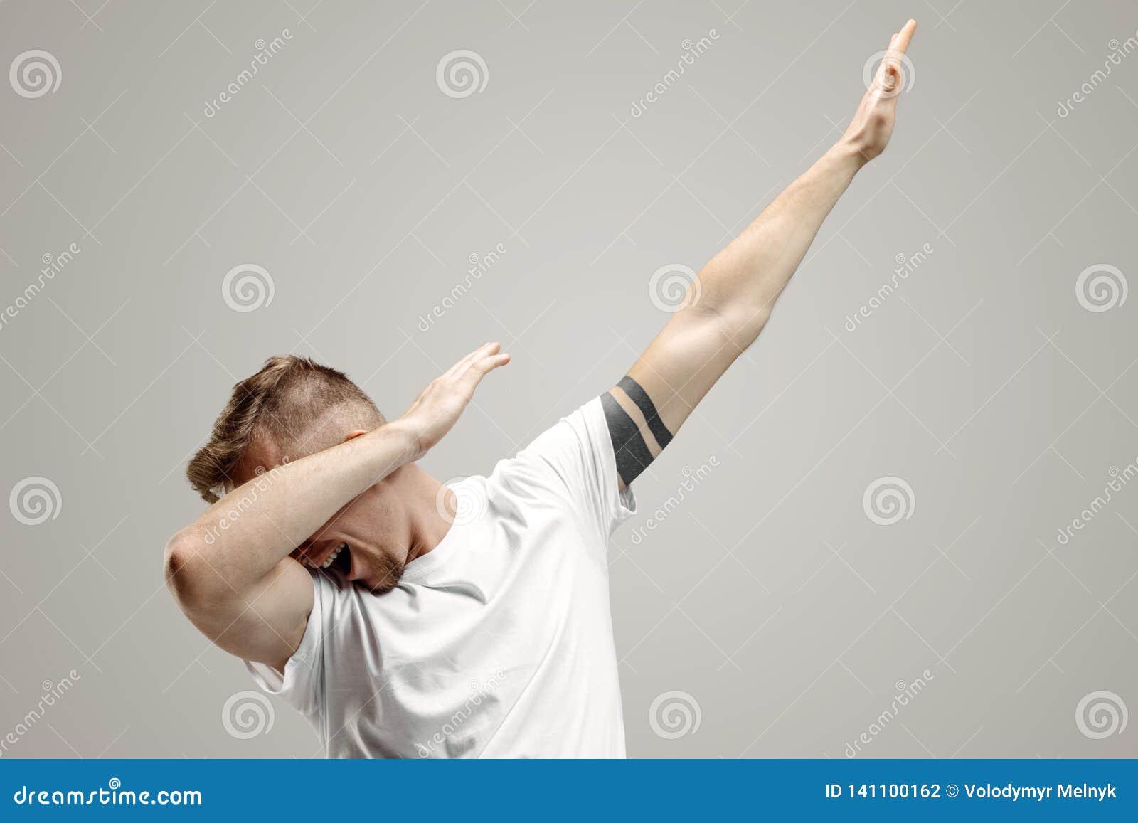 Młody człowiek robi odrobina ruchu z jego rękami na szarym tle