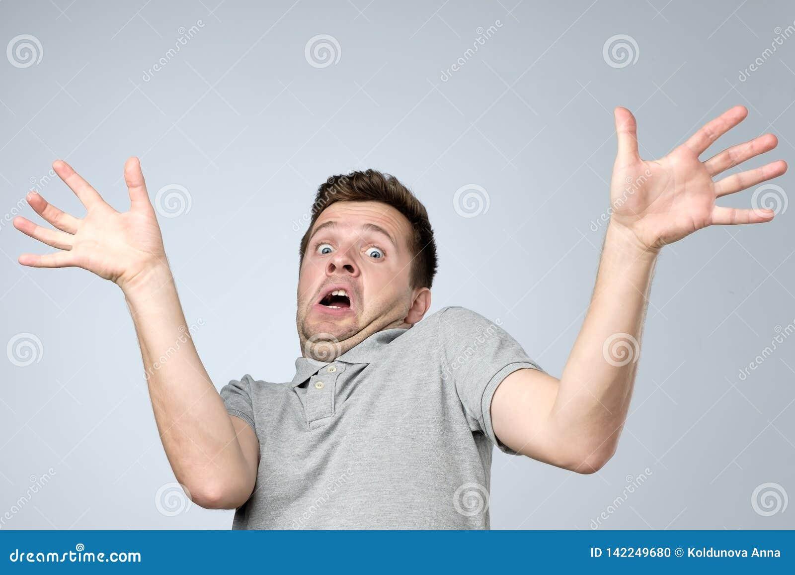 Młody europejski mężczyzna trzyma jego ręki outin strach na szarym tle