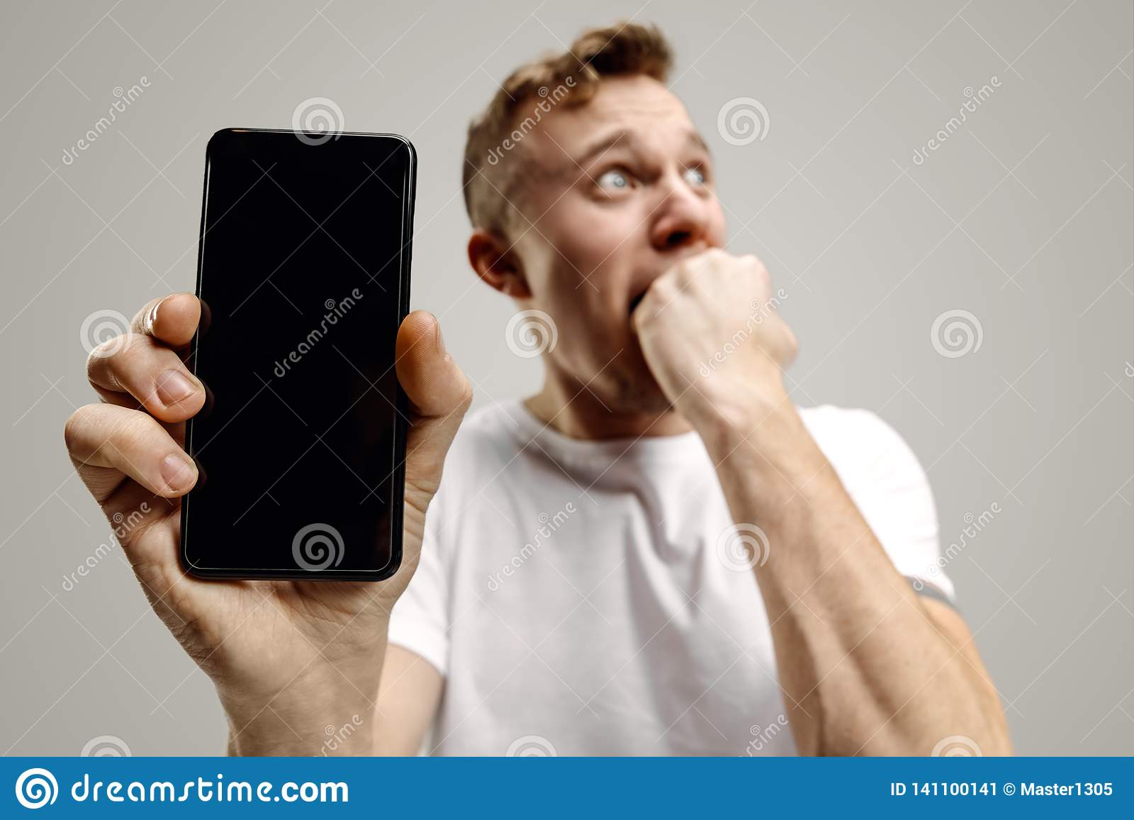 Młody przystojny mężczyzna pokazuje smartphone ekran odizolowywającego na szarym tle w szoku z niespodzianki twarzą