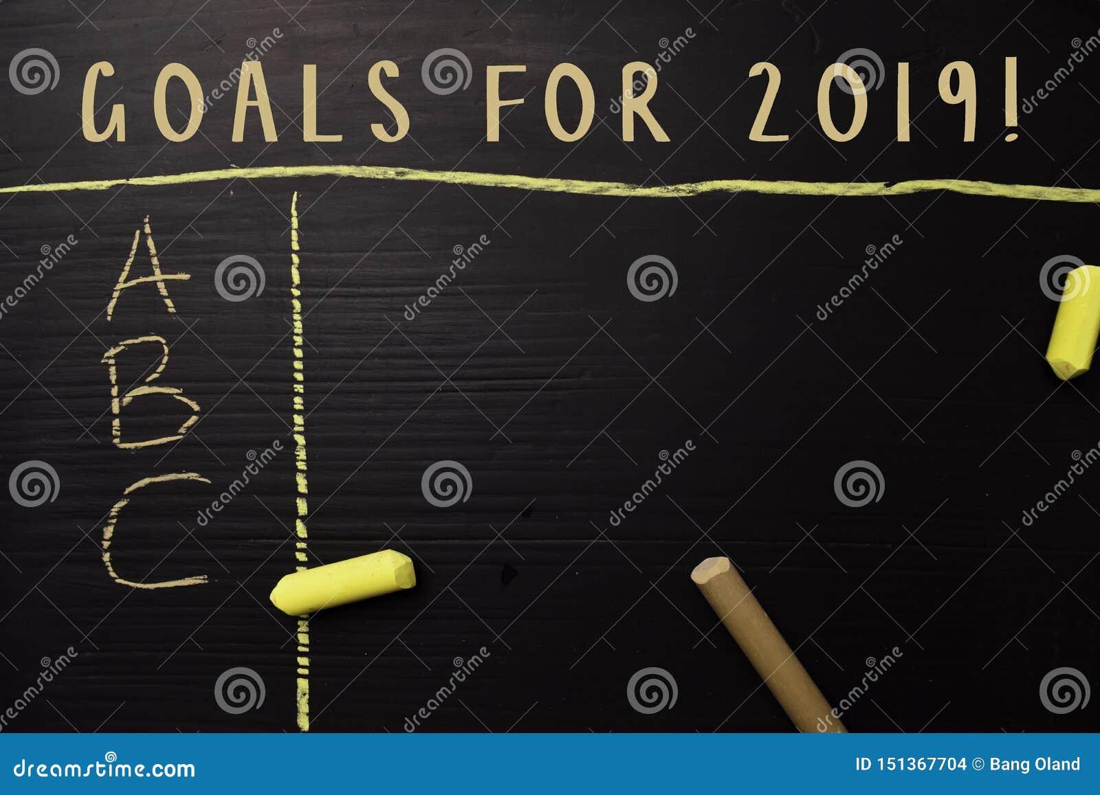 Mål för 2019! skriftligt med färgkrita Stöttat av extra service Svart tavlabegrepp