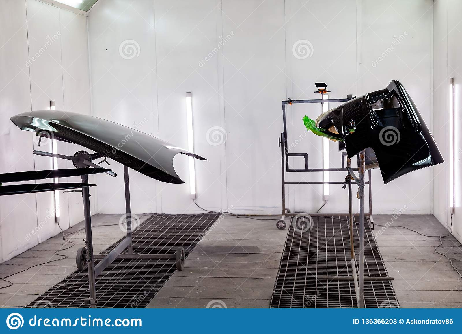 Måla och torka i en yrkesmässig ask av bilkroppsdelar, når att ha applicerat spackel och målarfärg på den svarta stötdämparen och
