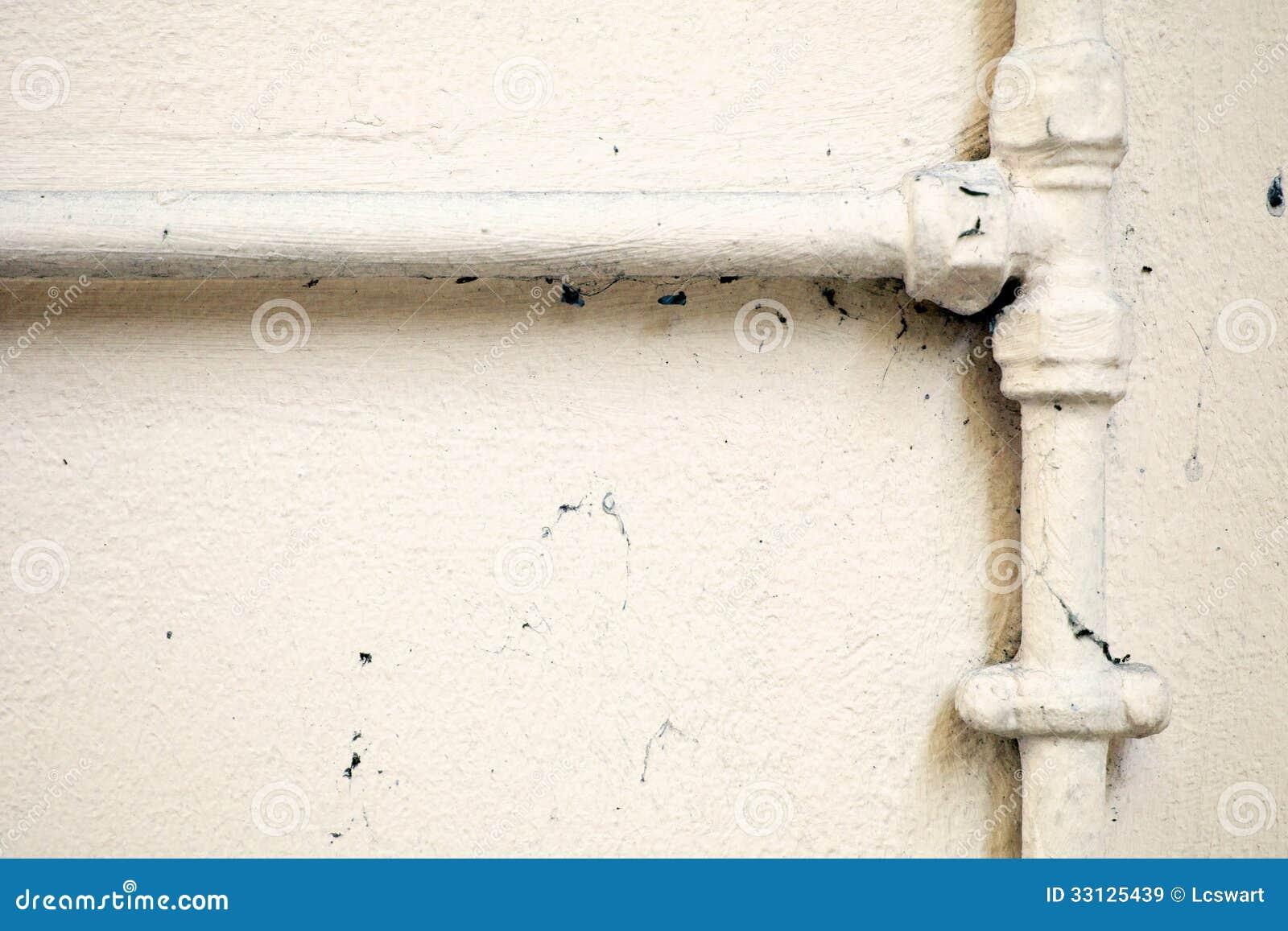 Målade rörmokerirör på väggen