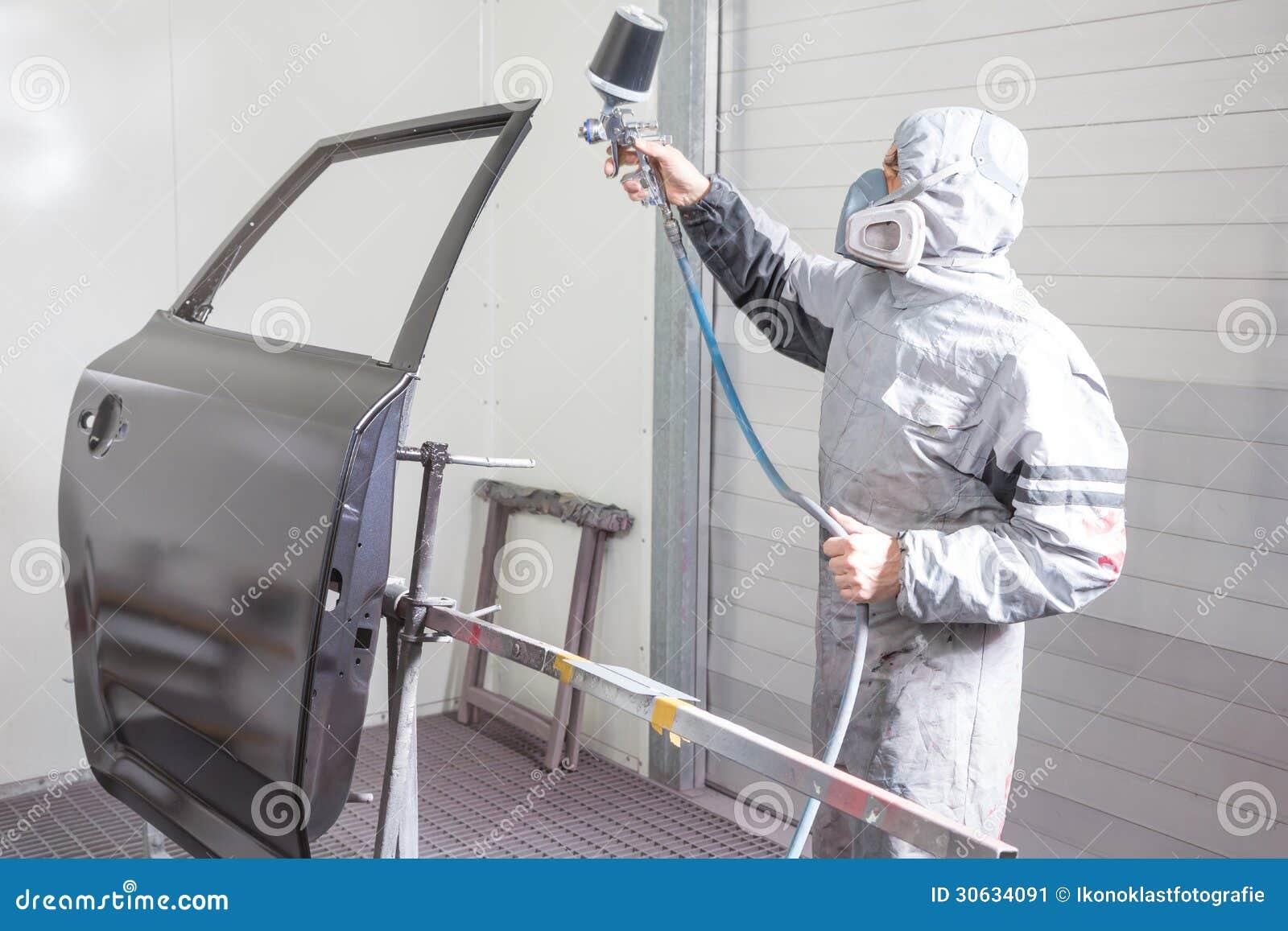 Målaren för bilkroppen som besprutar målarfärg på karosseri, särar