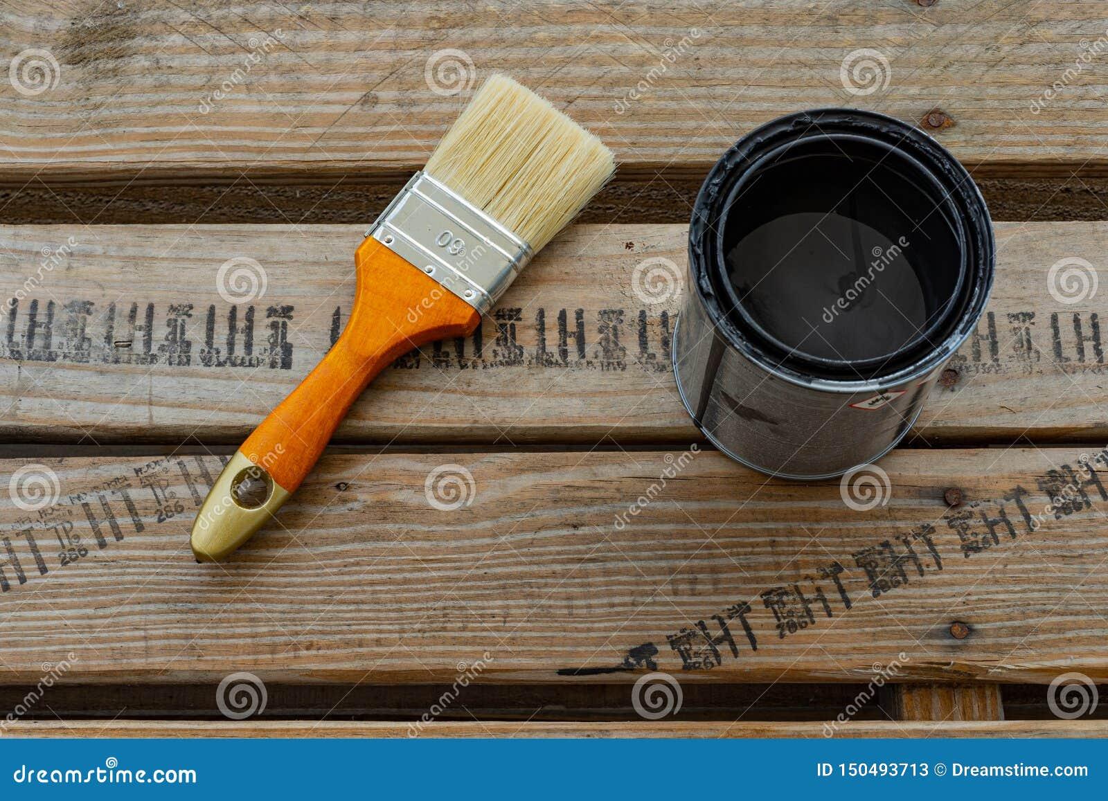 Målarpenseln och kan med färg för hem- renovering