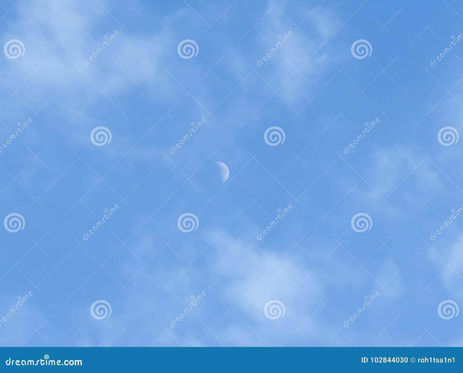 Måne under dag i den blåa himlen mellan moln