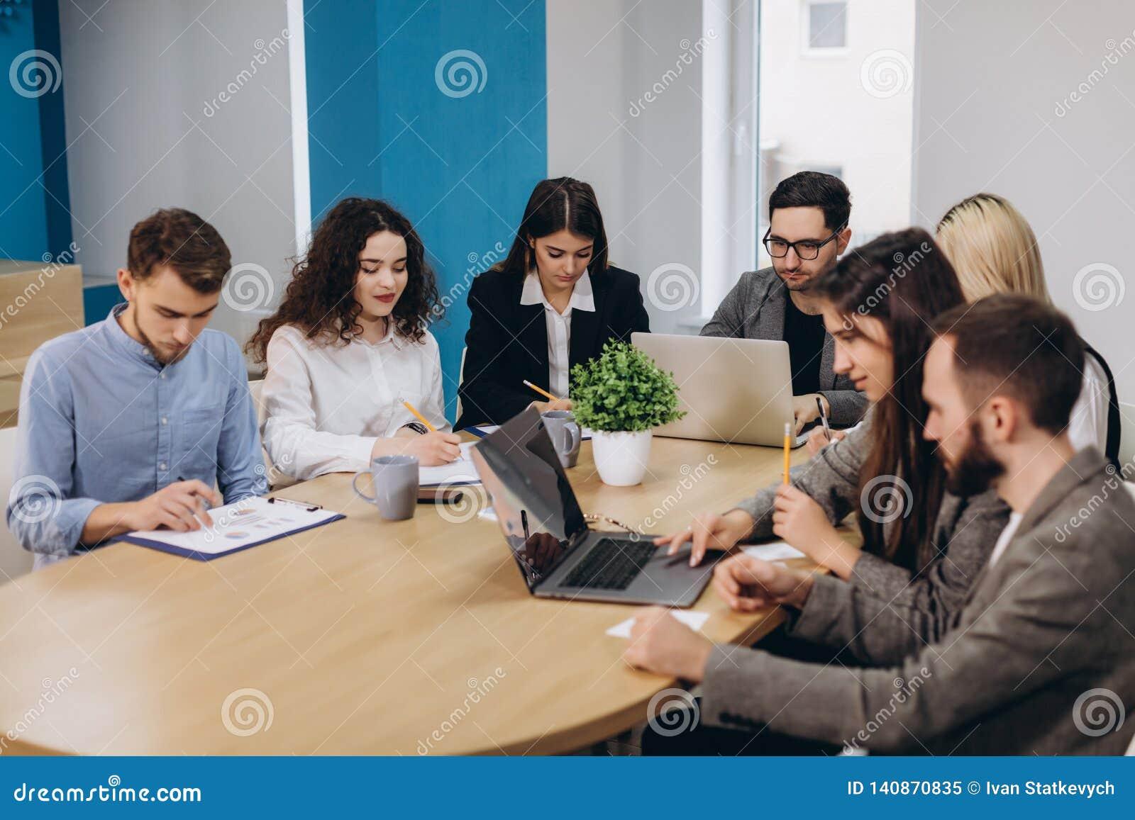 Mång- etnisk folkentreprenör, små och medelstora företagbegrepp Kvinna som visar coworkers något på bärbar datordatoren, som de s
