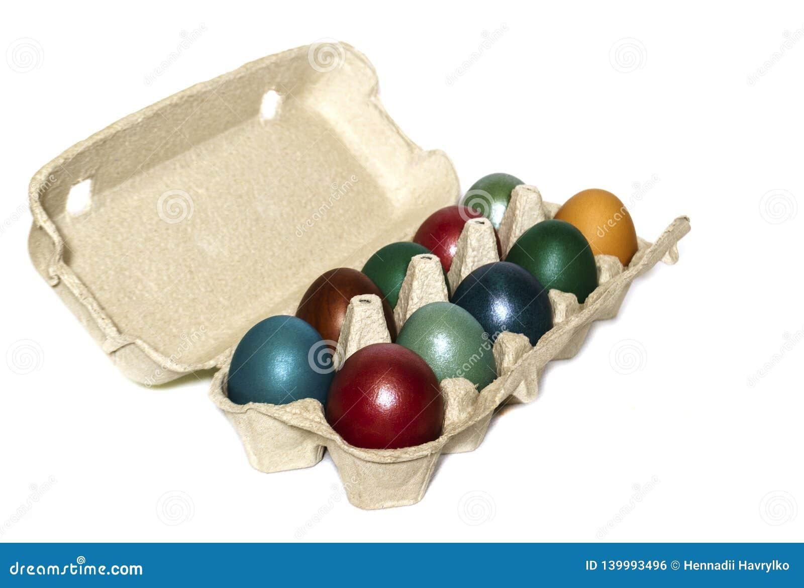 Mång--färgade ägg i ett magasin på en vit bakgrund