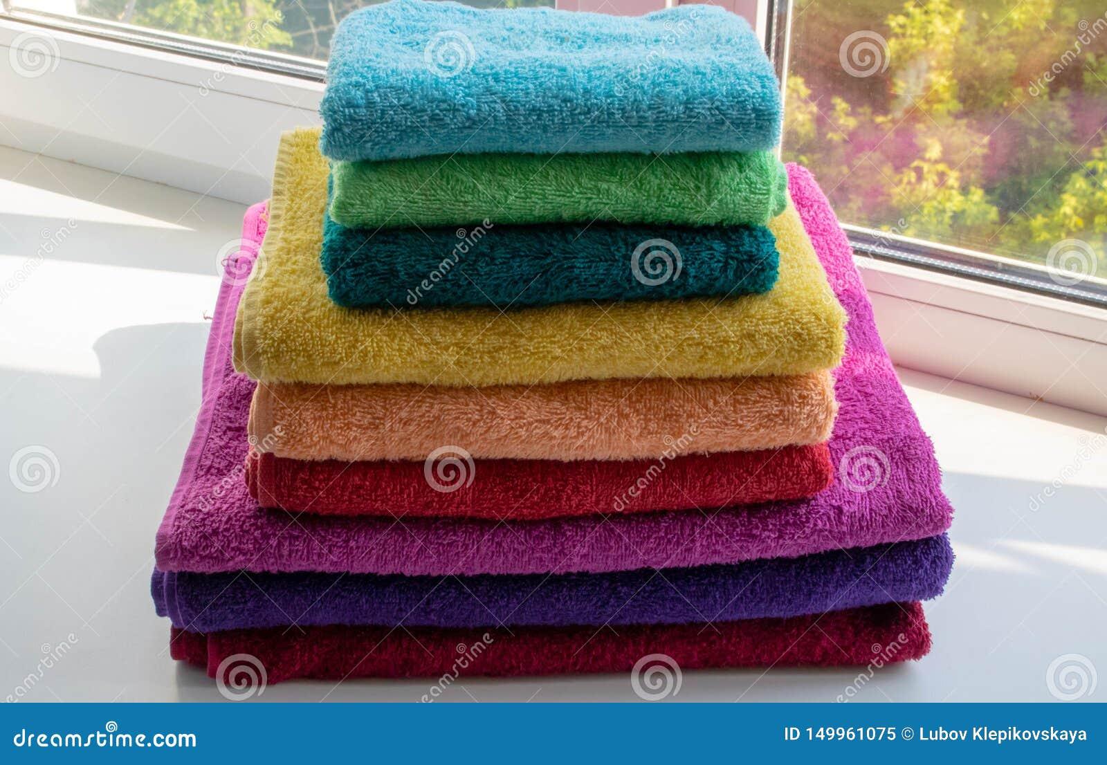 Mång--färgade dubbla handdukar i en bunt på fönstret