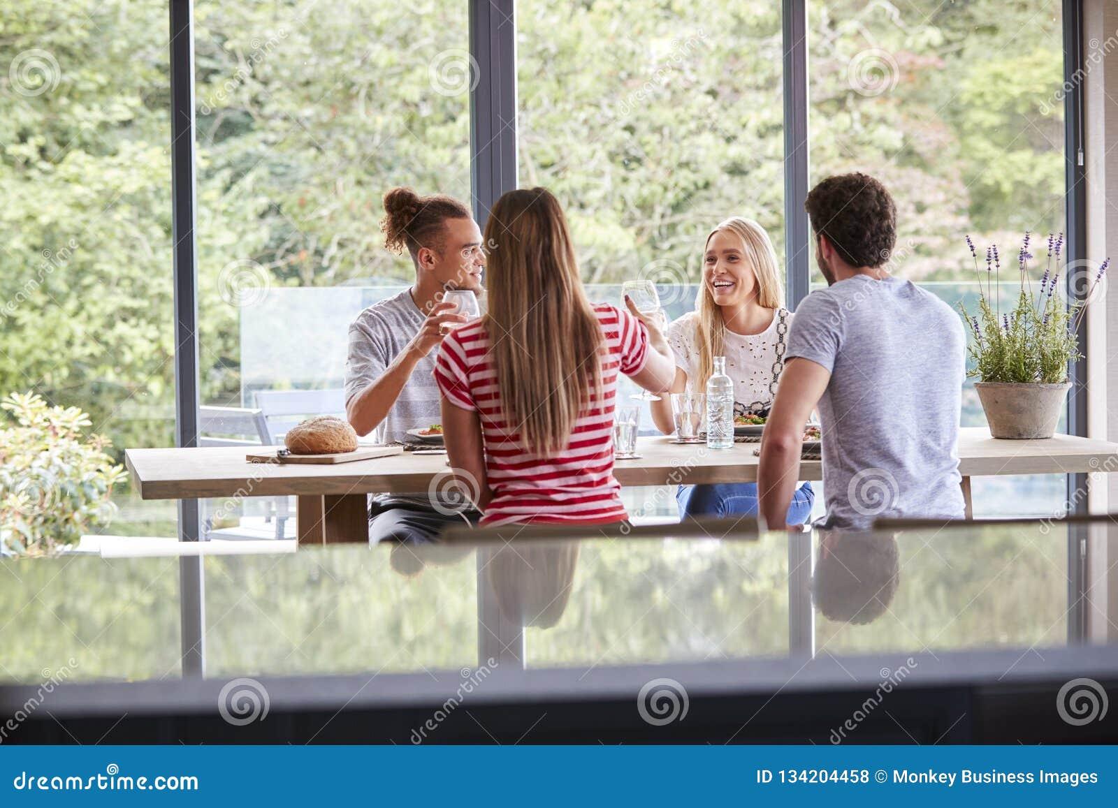 Mång- folkgrupp av fyra unga vuxna vänner som firar på ett matställeparti som lyfter deras vinexponeringsglas som ses från kökön