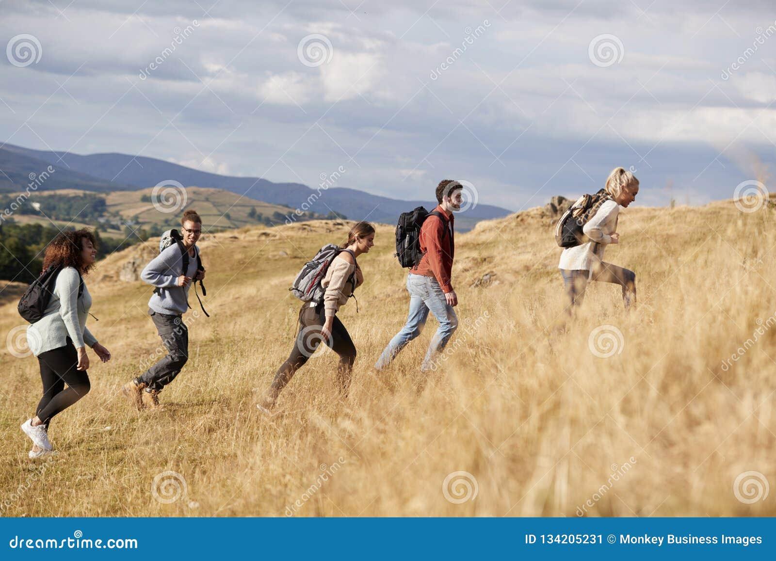 Mång- folkgrupp av lyckliga unga vuxna vänner som klättrar en kulle under en bergvandring, sidosikt