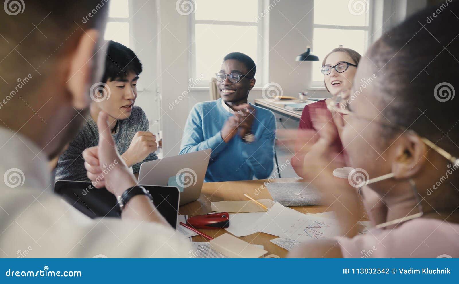 Mång- folkgrupp på kontorsaffärsmötet Unga olika partners diskuterar idéer, då startar att applådera och att le 4K lager videofilmer
