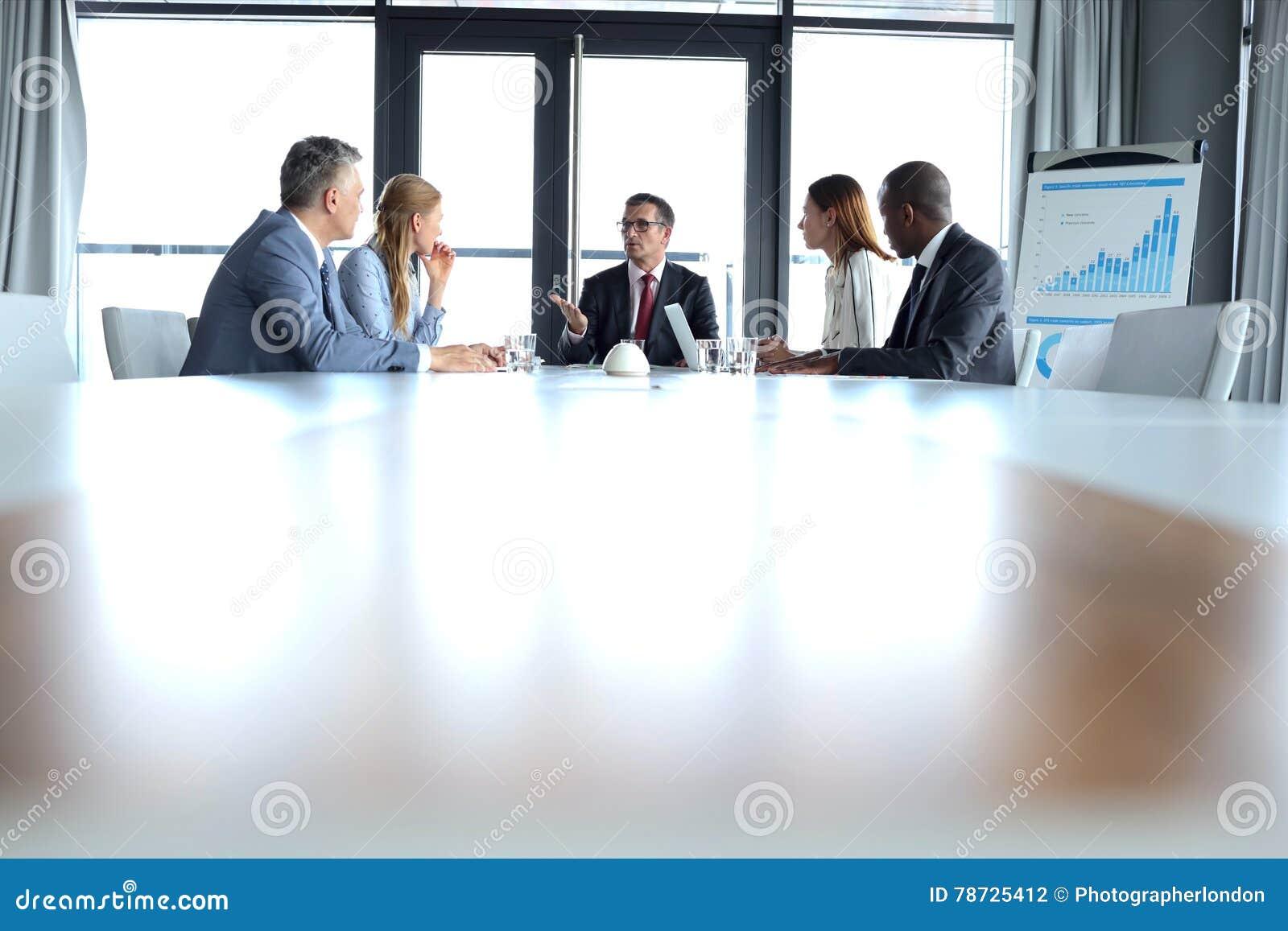 Mång--person som tillhör en etnisk minoritet affärsfolk som har diskussion på tabellen i bräderum