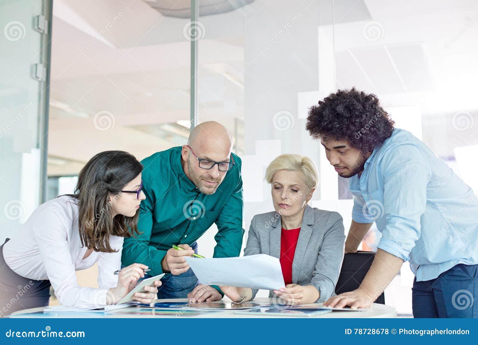 Mång--person som tillhör en etnisk minoritet affärsfolk som i regeringsställning diskuterar över dokument på tabellen