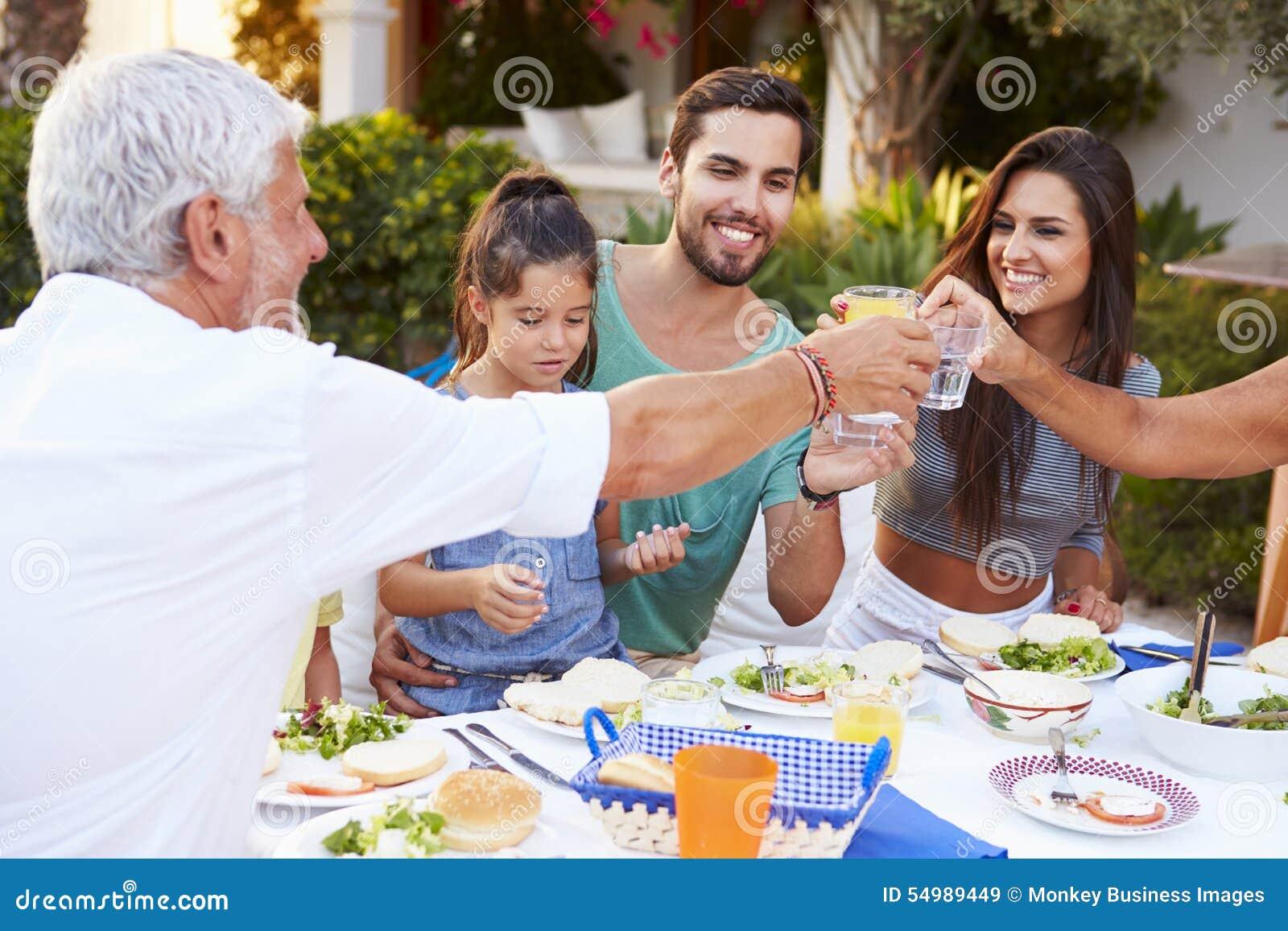 Mång- utvecklingsfamilj som tillsammans äter mål på det fria
