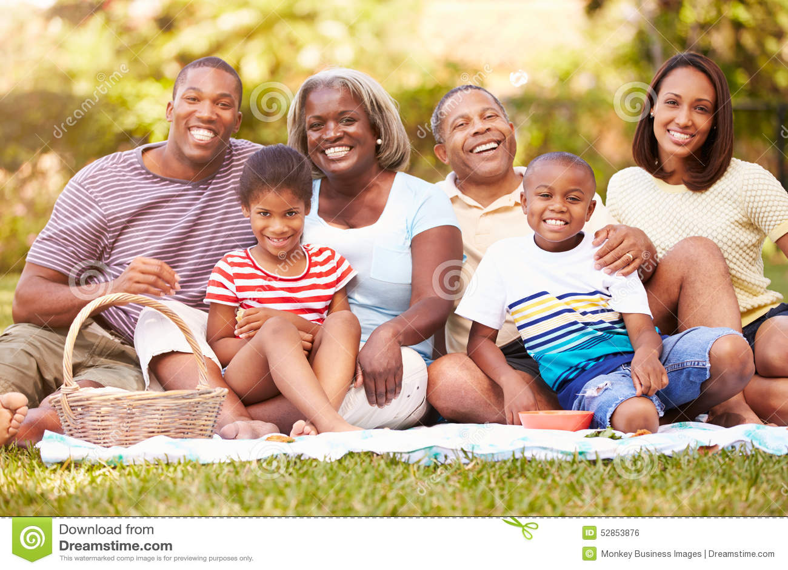 Mång- utvecklingsfamilj som tillsammans tycker om picknicken i trädgård