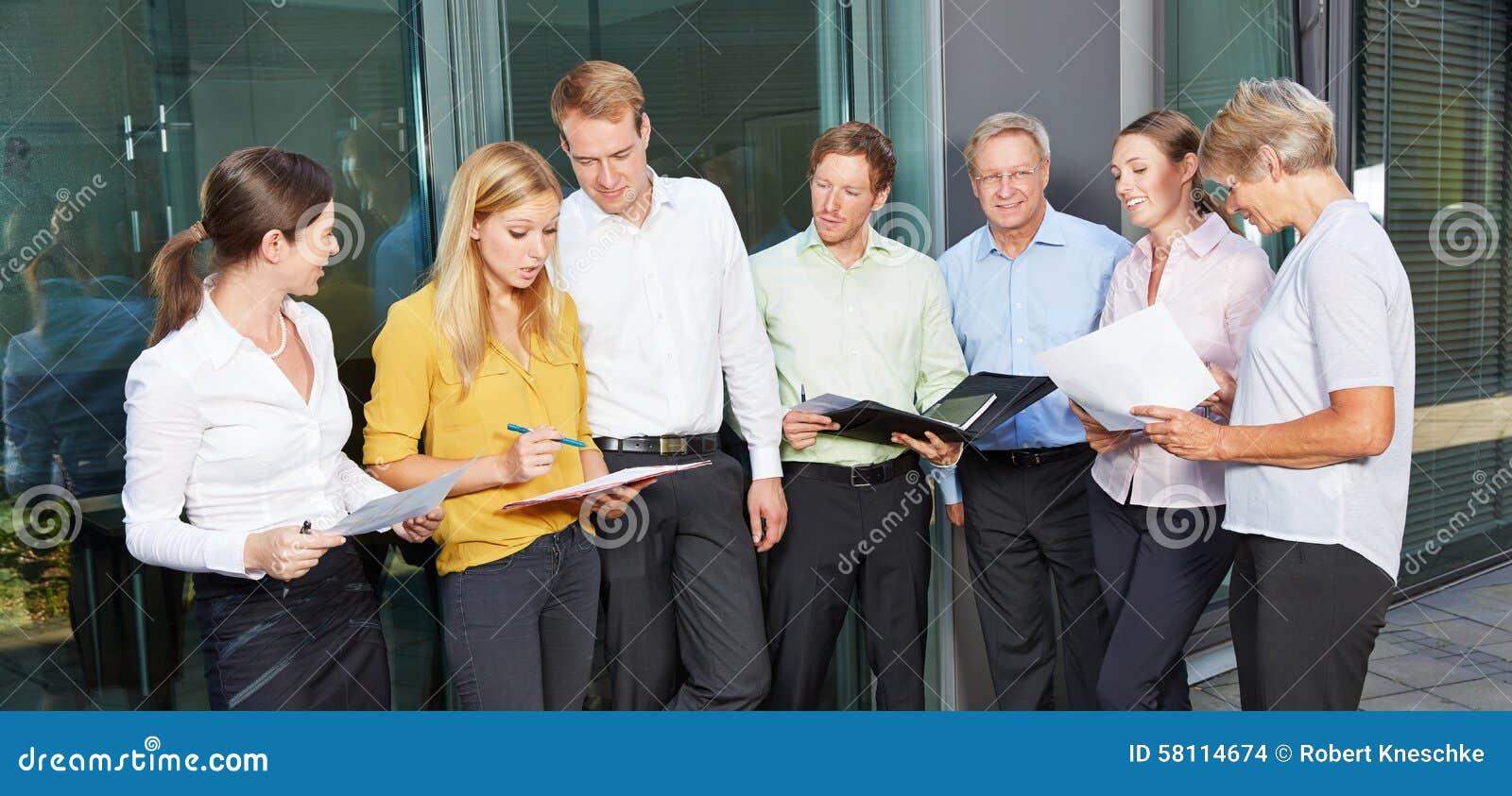 Många affärspersoner som står utanför kontoret