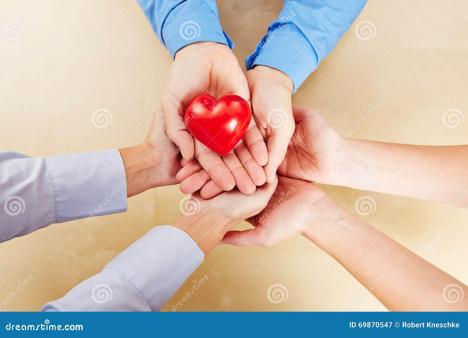 Många händer som rymmer en röd hjärta