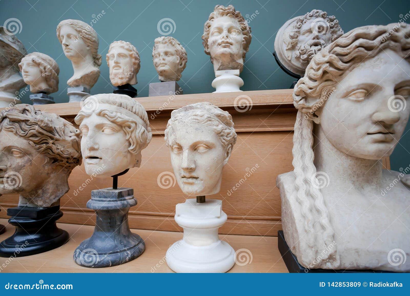 Många mänsklig framsida- och marmorhuvudkopior av gamla romerska gudar och kejsare på hylla Minnen om människa av den forntida vä