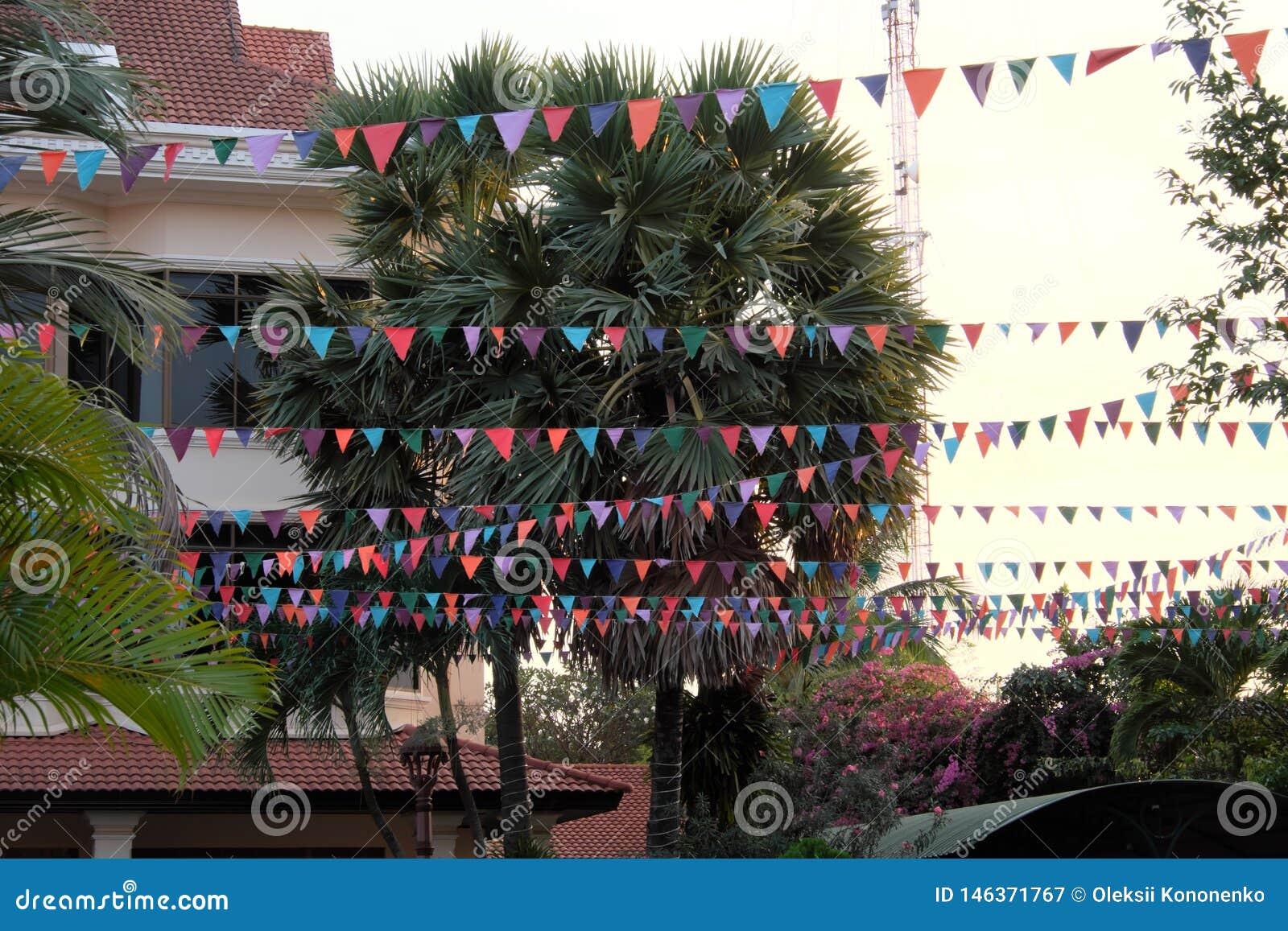Många mångfärgade flaggor dekorerar gatan Dekorativa girlander tropiska trees