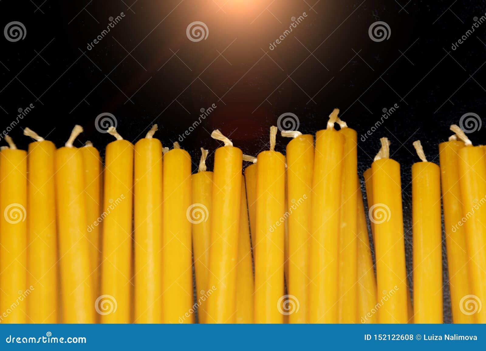 Många naturliga tunna gula vaxstearinljus ligger på svart bakgrund