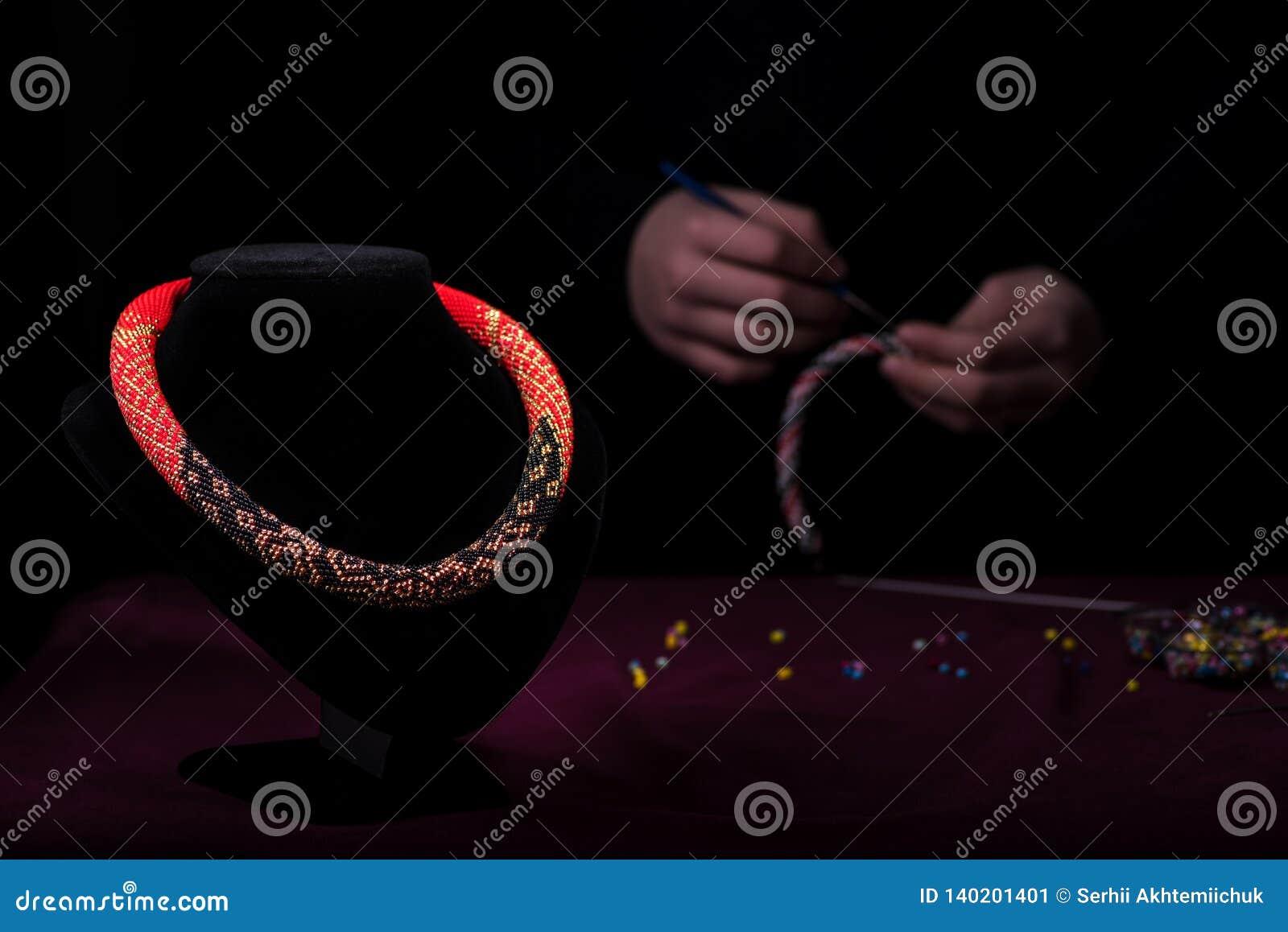Mångfärgad halsband av pärlor på en skyltdocka På den tillbaka svarta nivån sticker flickan pärlorna