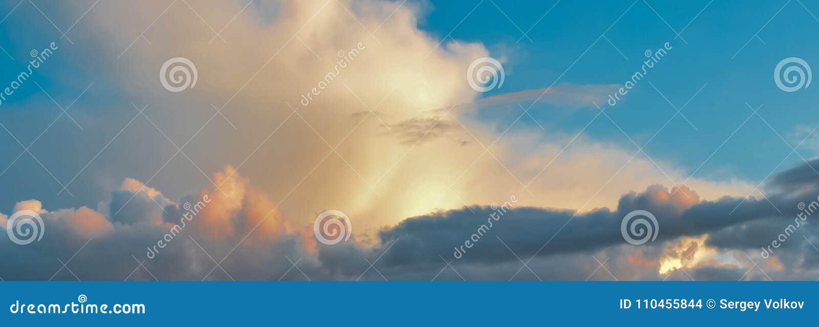 Mångfärgade moln i den blåa himlen