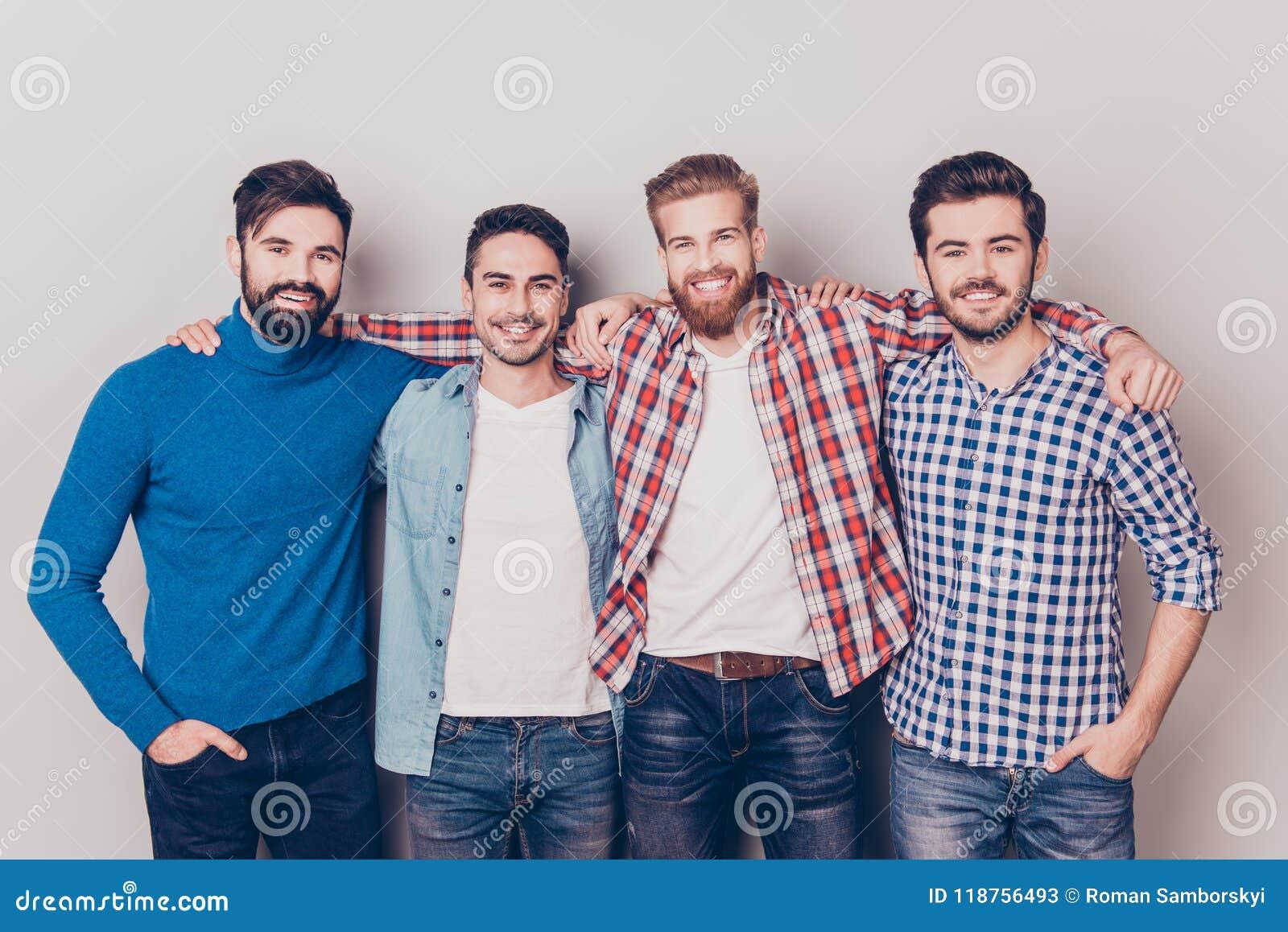 Mångfald av män Fyra gladlynta unga grabbar står och embr